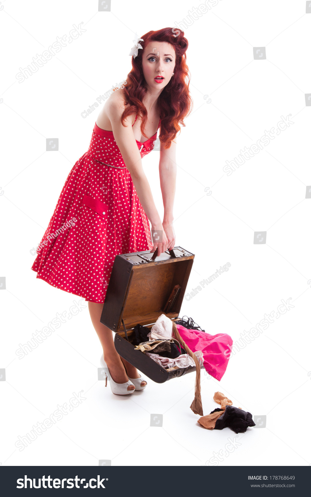 Beautiful retro pin-up girl with red polka dot dress and suitcase with  clothes falling 1f9df48980f6