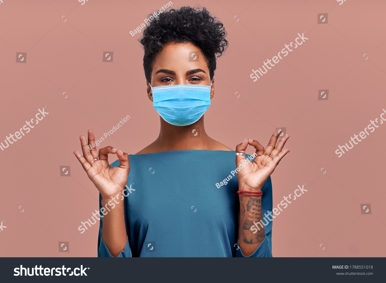 Kind Hearted African American Female Paramedic Wearing Respiratory Mask from Coronavirus Disease During COVID-19 Epidemic, Says Good Job or Well Done, Makes Okay Gesture, Symbol of Approval and Like #1788551018