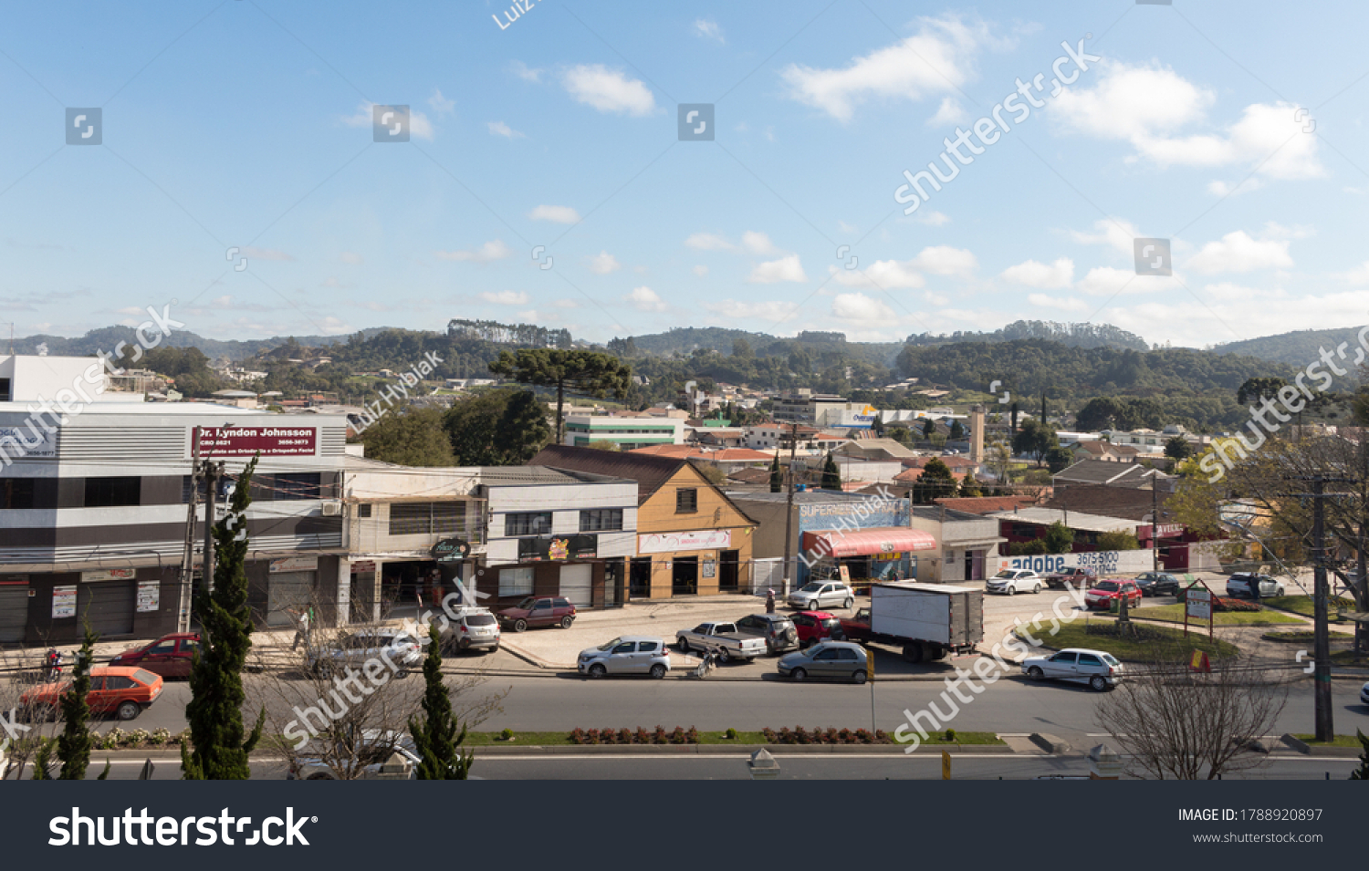Colombo, Paraná, Brazil - August 01, 2020. City downtown with some small business on the main street. Trees and mountains in the horizon. Parked cars.