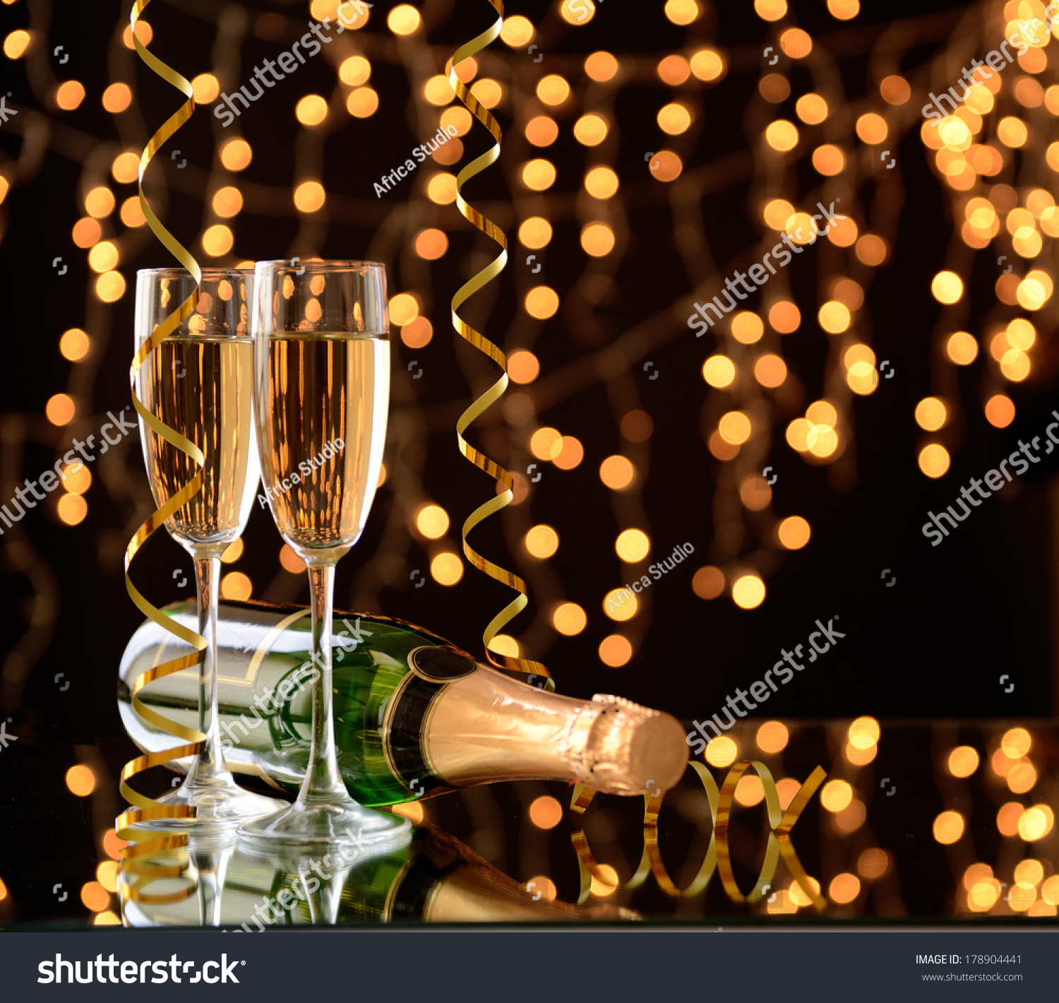 Glasses and bottle of champagne on shiny background #178904441