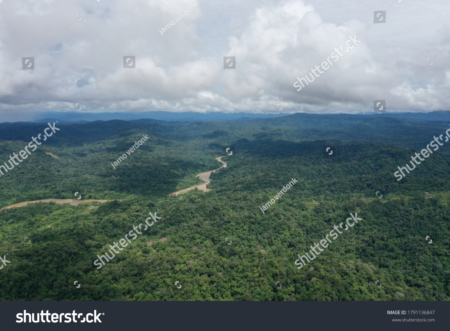 Aerial view of the Amazon with a large brown river meandering through the landscape and shadows of clouds over the rainforest