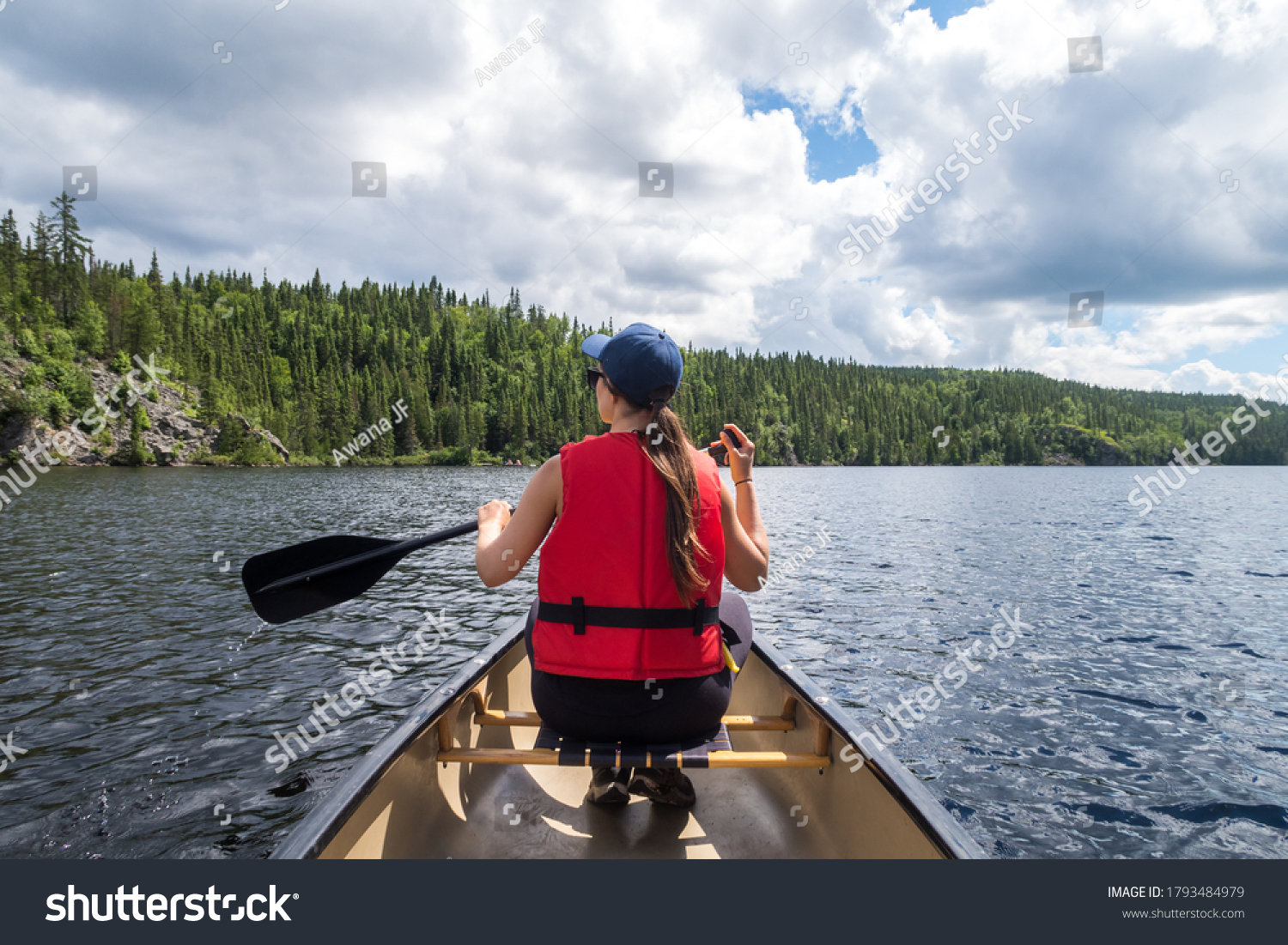 Back view of a young woman rowing  a canoe at the Aiguebelle national park, Quebec