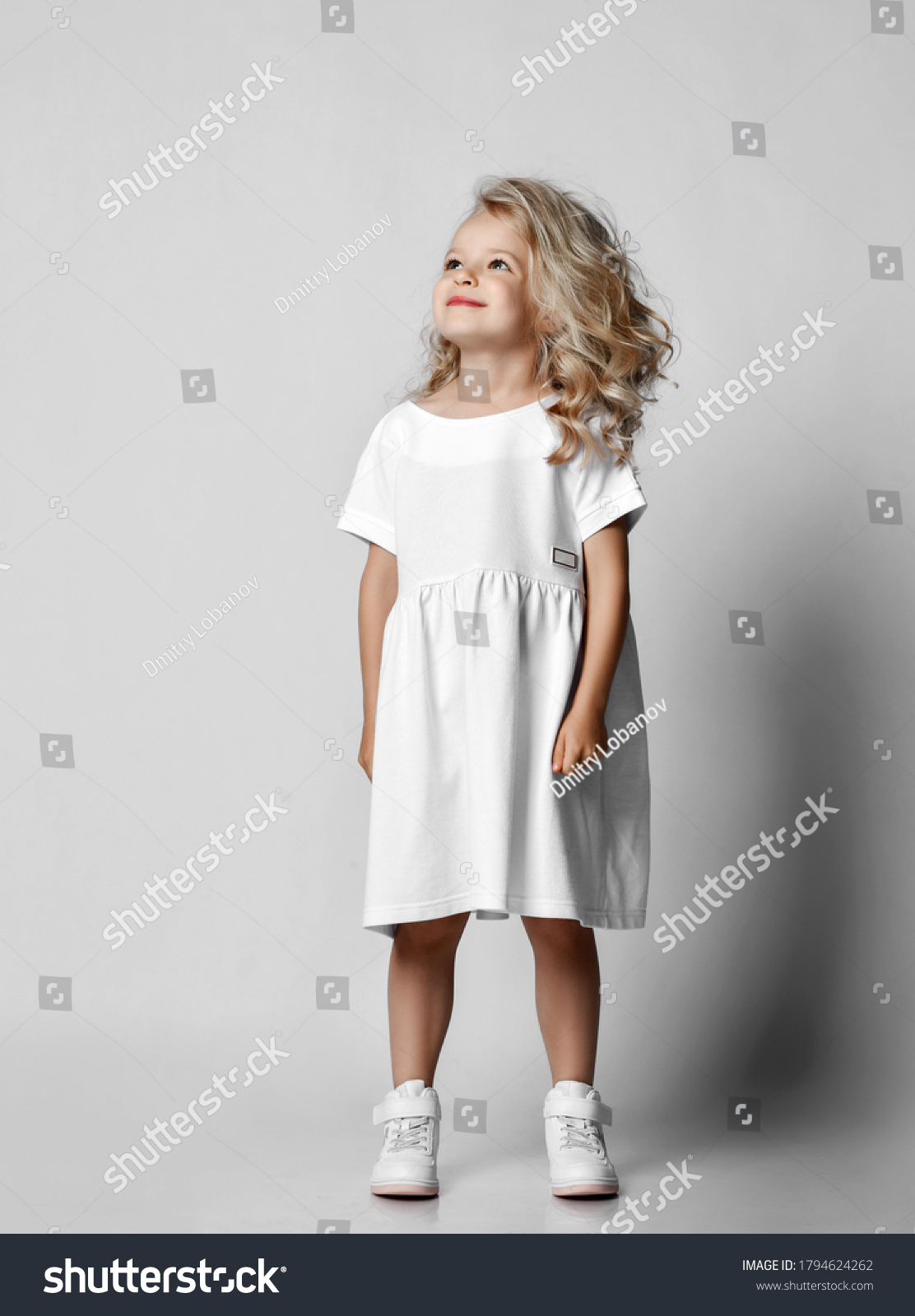 Smiling positive little blonde curly kid girl in white casual dress and sneakers is looking at copy space at upper corner. Stylish comfortable everyday fashion for children concept #1794624262