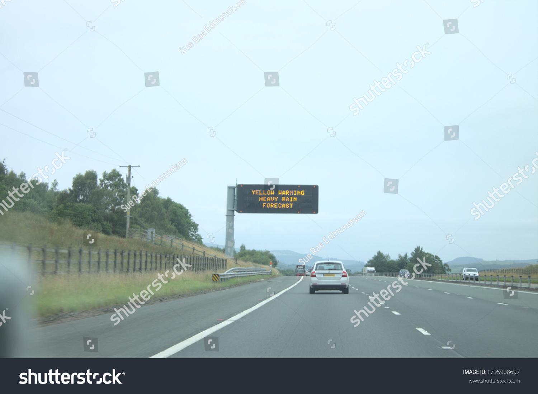 Moffat, Scotland, UK, 14/08/2020: Yellow warning heavy rain forecast sign on motorway