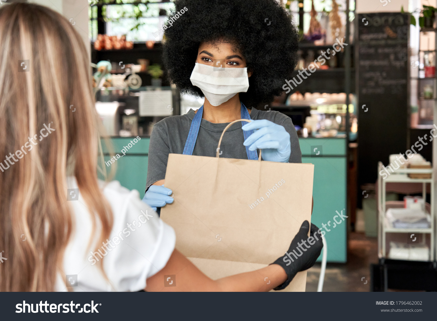 African American female cafe worker wears face mask and gloves giving takeaway food bag to customer. Mixed race waitress holding takeout order standing in coffee shop restaurant with take away client. #1796462002
