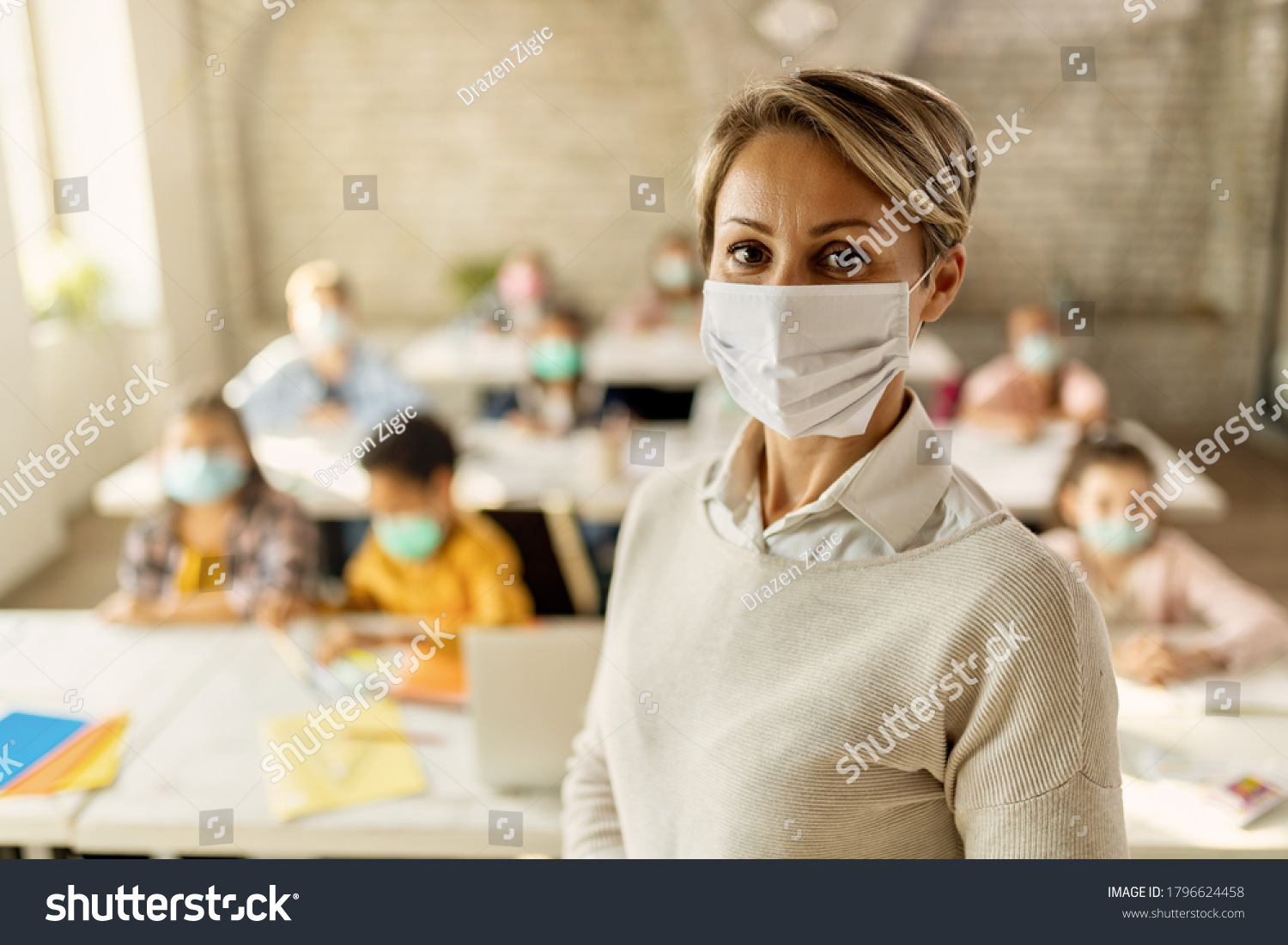 Female teacher wearing a face mask while teaching children at elementary school and looking at camera.  #1796624458