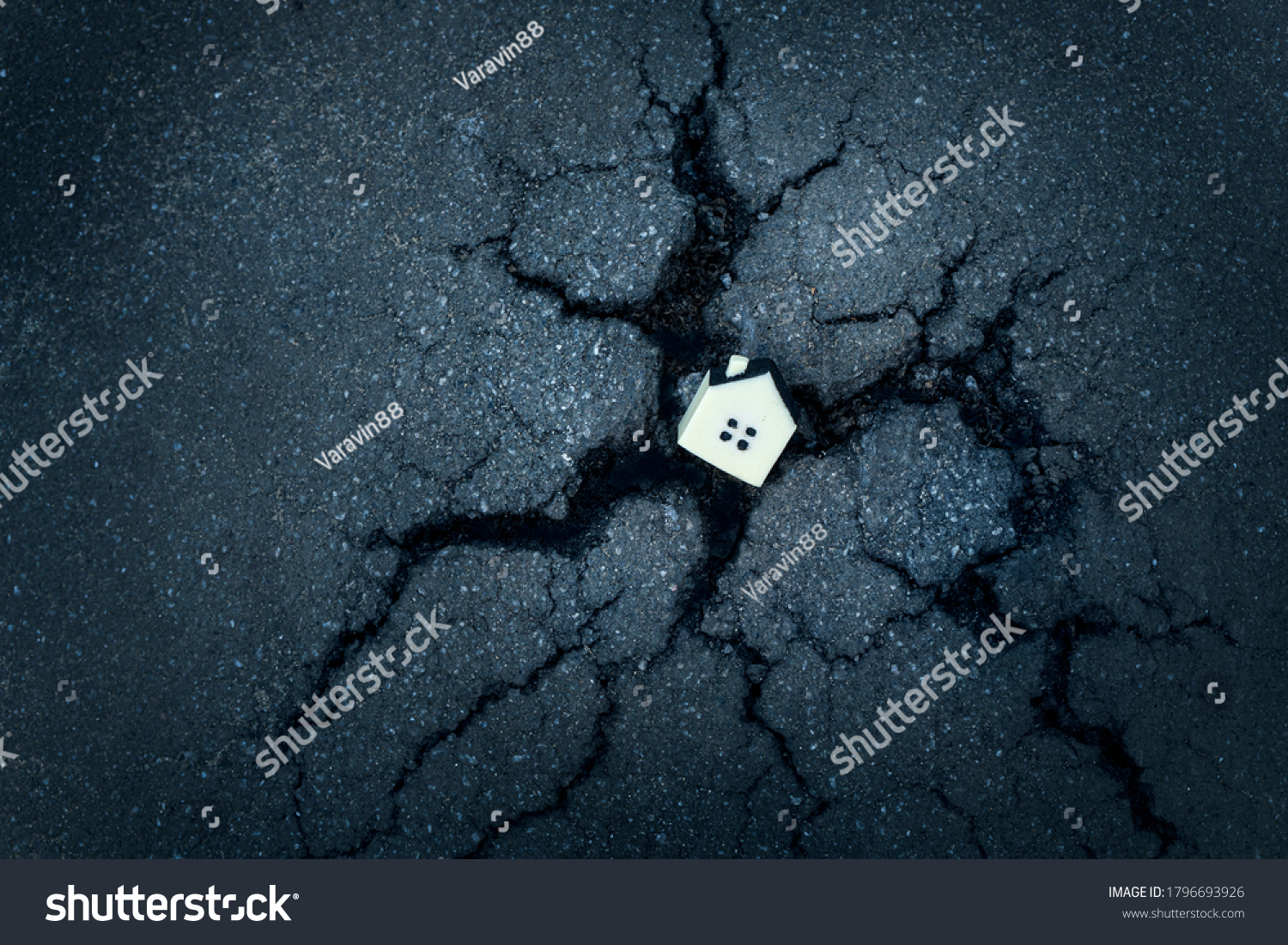 Destruction of residential buildings concept with the little toy house in a cracked asphalt hole. #1796693926