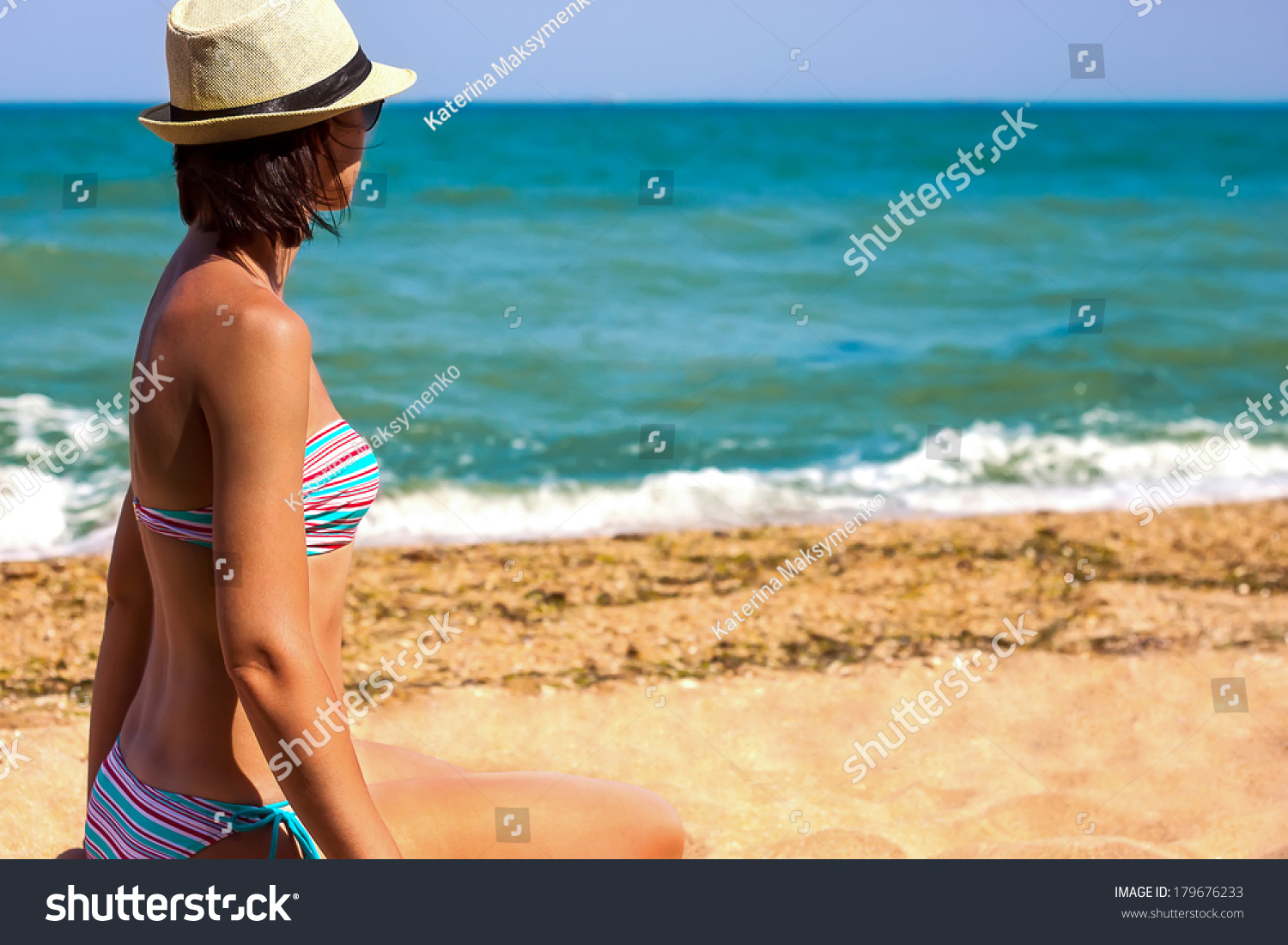 young woman in a straw hat sitting on the sea beach and looks at the sea #179676233