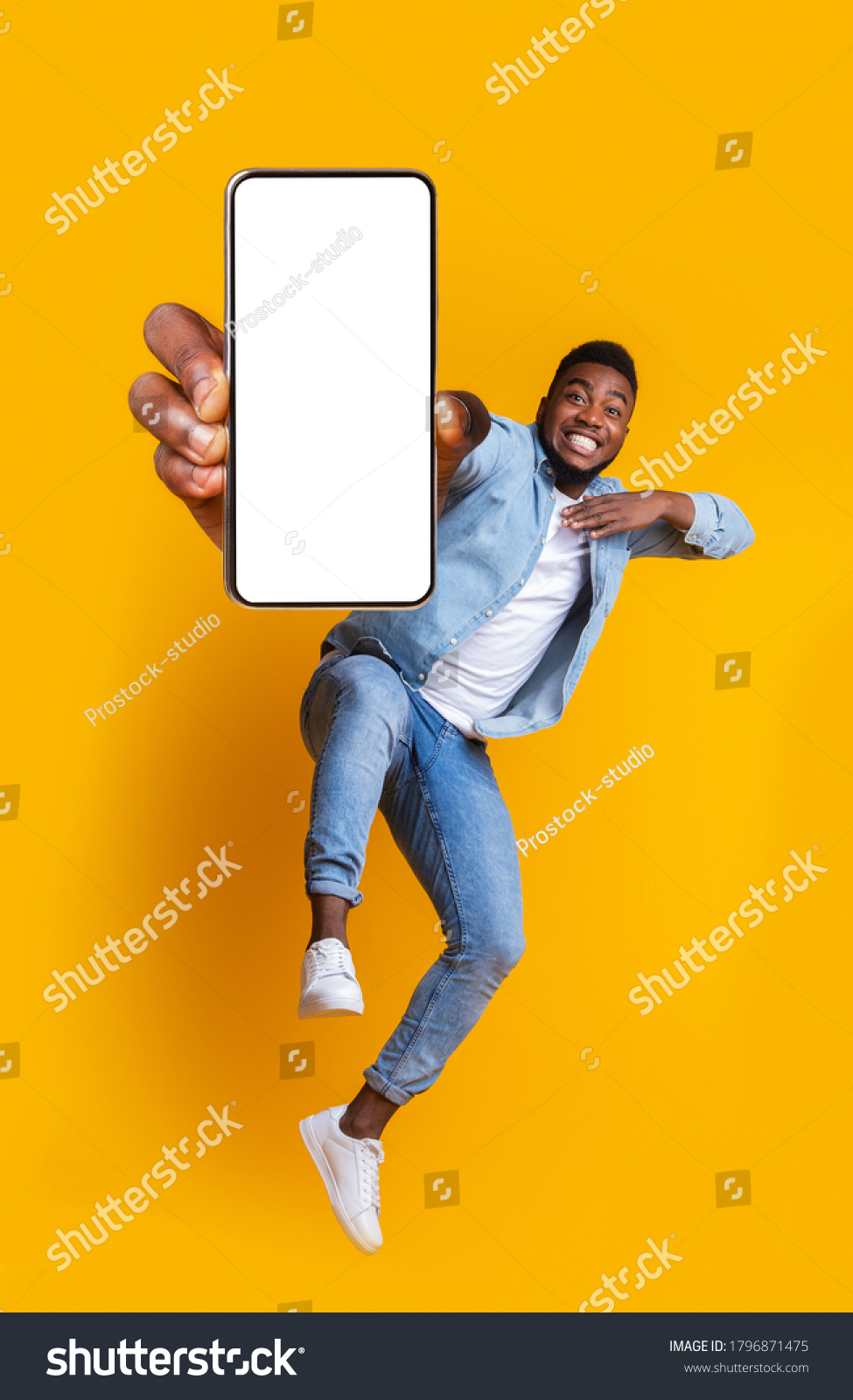 Advertisement for mobile application. Excited african guy dancing over yellow background, showing modern smartphone with empty screen, collage #1796871475
