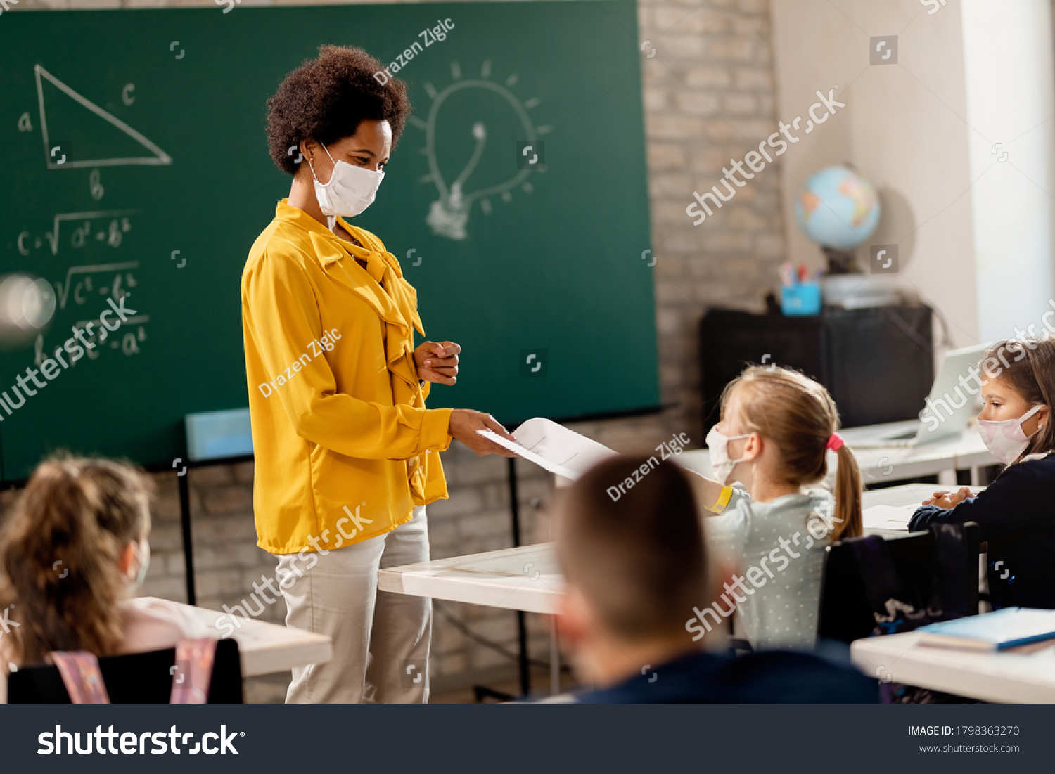 Happy black teacher and her students wearing protective face mask in the classroom. Teacher is giving them their test results.  #1798363270