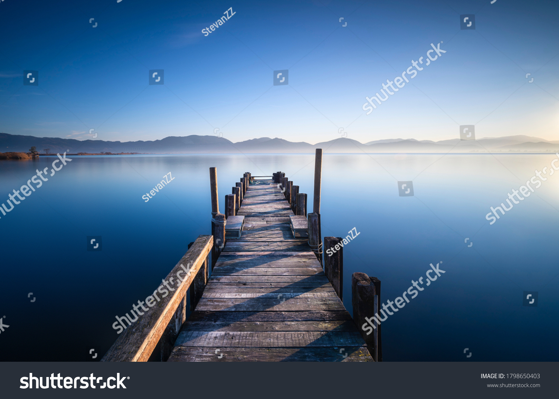 Wooden pier or jetty and lake at sunrise. Torre del Lago Puccini, Versilia, Massaciuccoli lake, Tuscany, Italy, Europe #1798650403