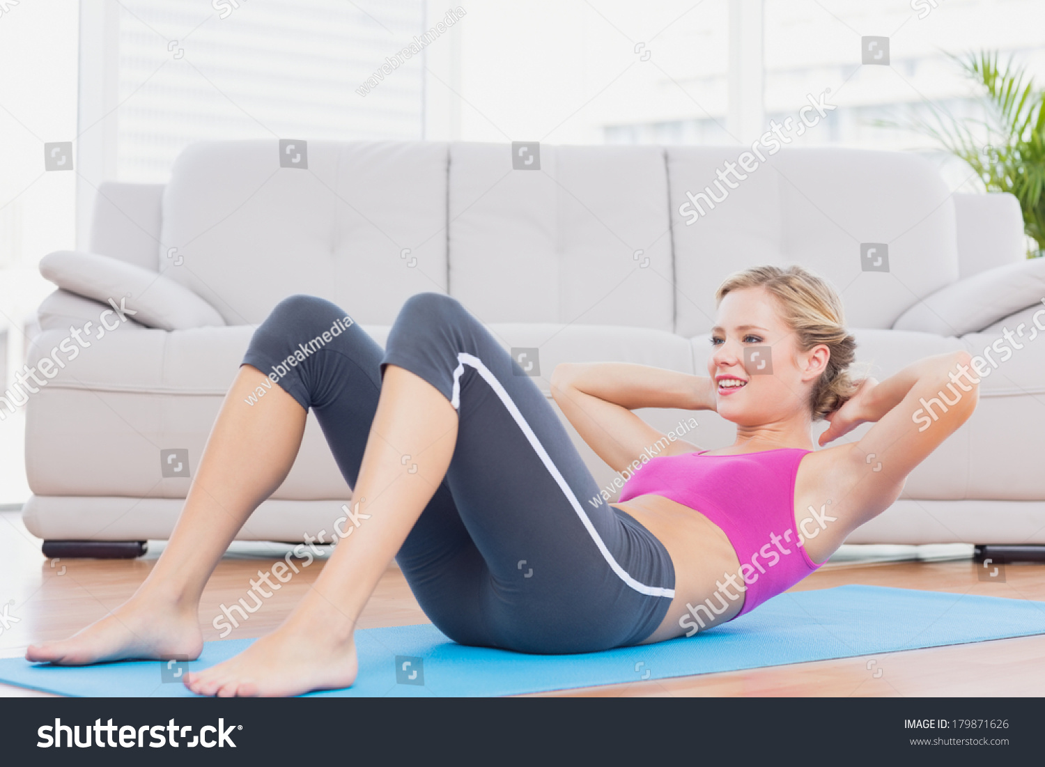Slim Blonde Doing Sit Ups On Exercise Mat At Home In The Living Room 179871626