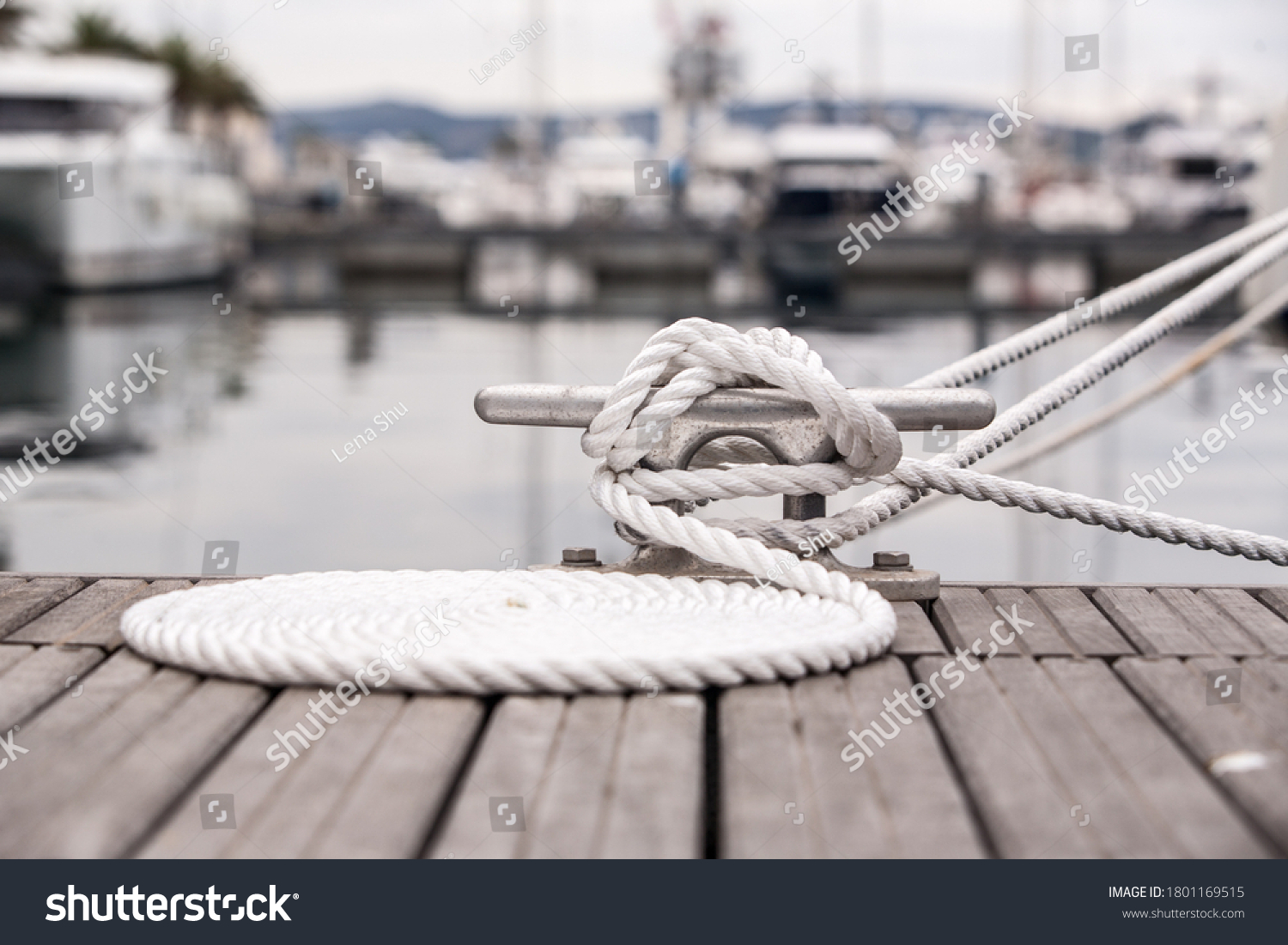 Nautical mooring line rope on the jetty. Curled mooring line. #1801169515