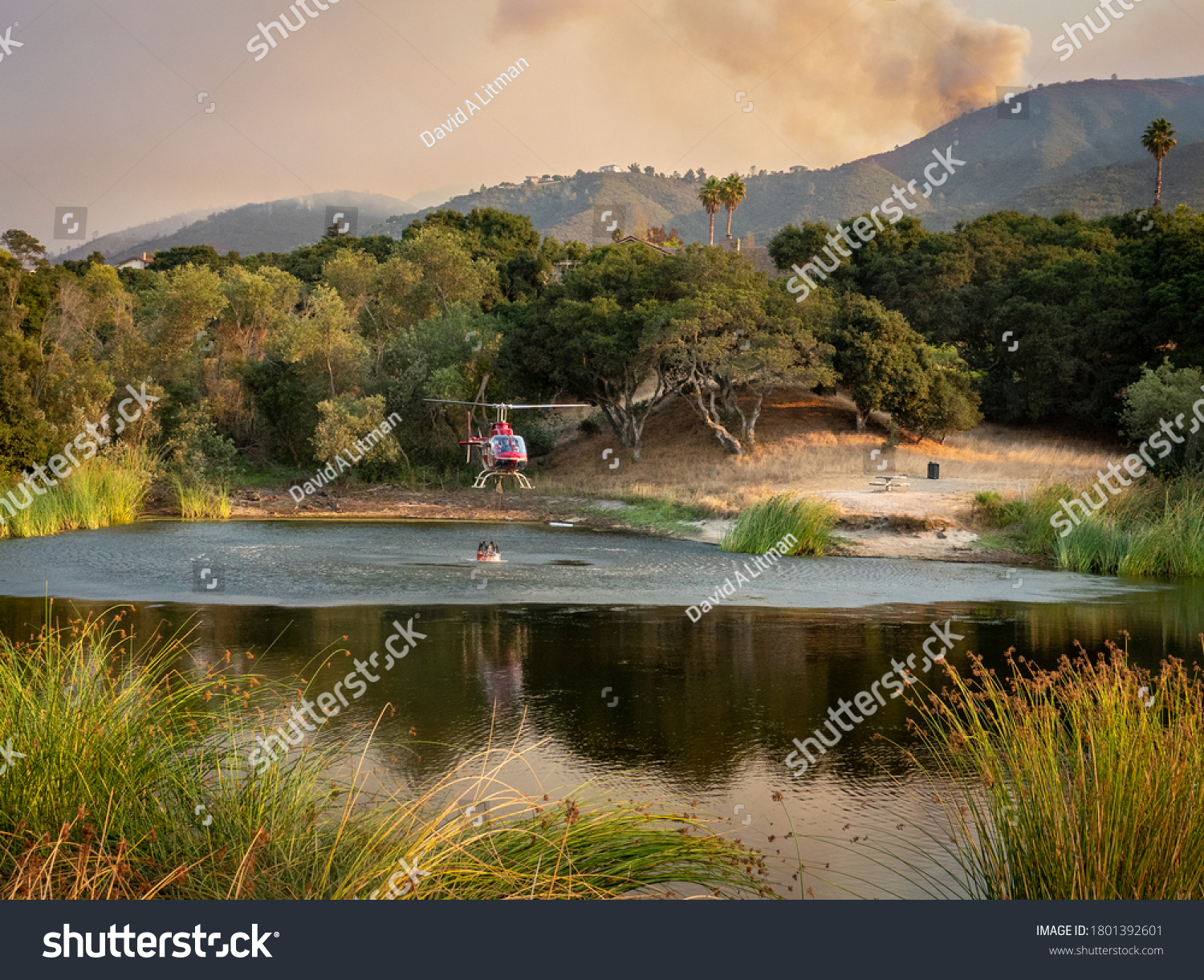 """A helicopter pilot collects a bucket of water from a pond to douse the """"River Fire"""" in the hills Monterey County of the central coast of California as plumes of smoke drift upward."""