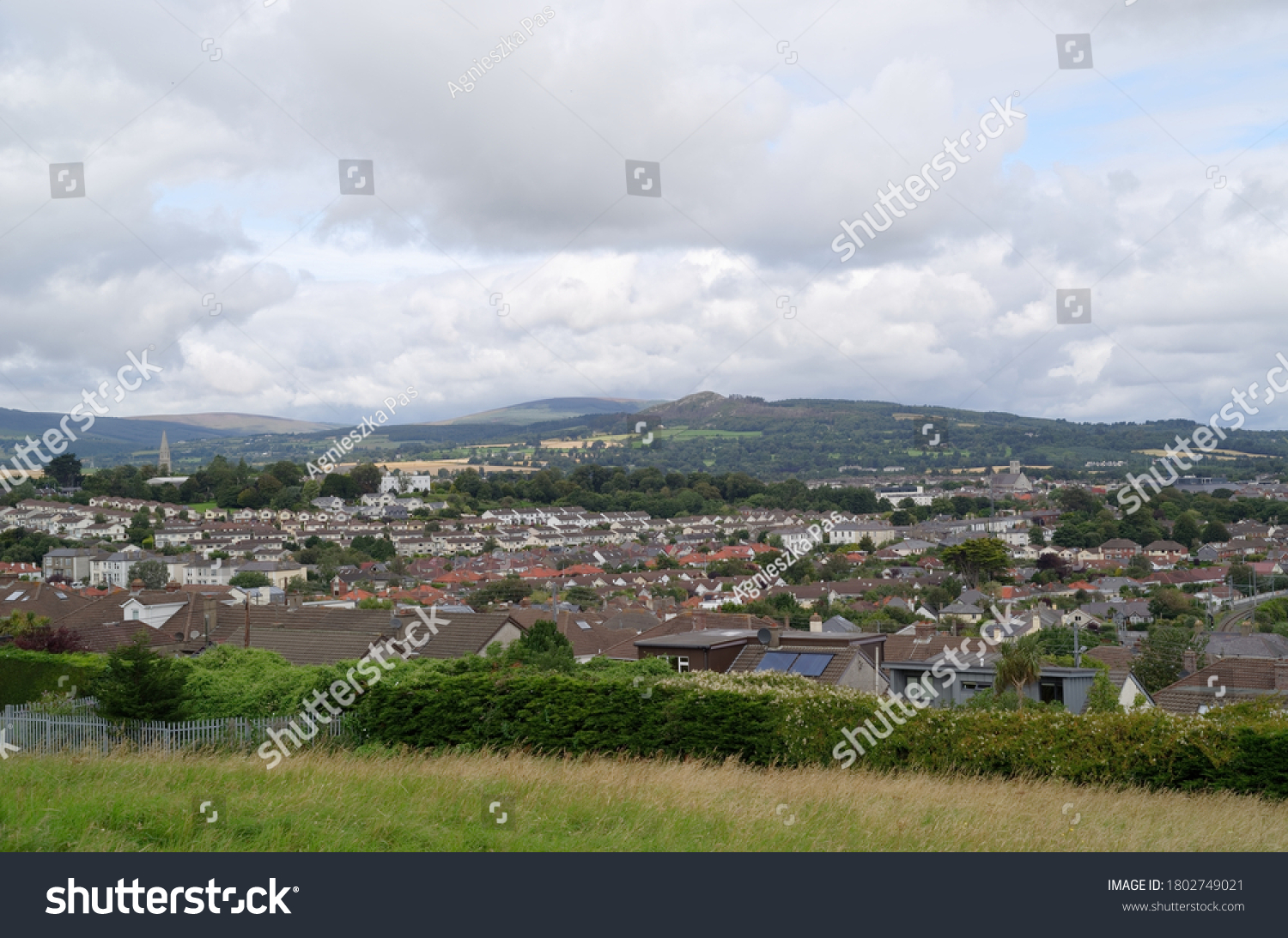 View of Bray town in County Wicklow, Ireland, on cloudy summer day. Town surrounded by mountains. View from the hill. Landscape with roof tops.