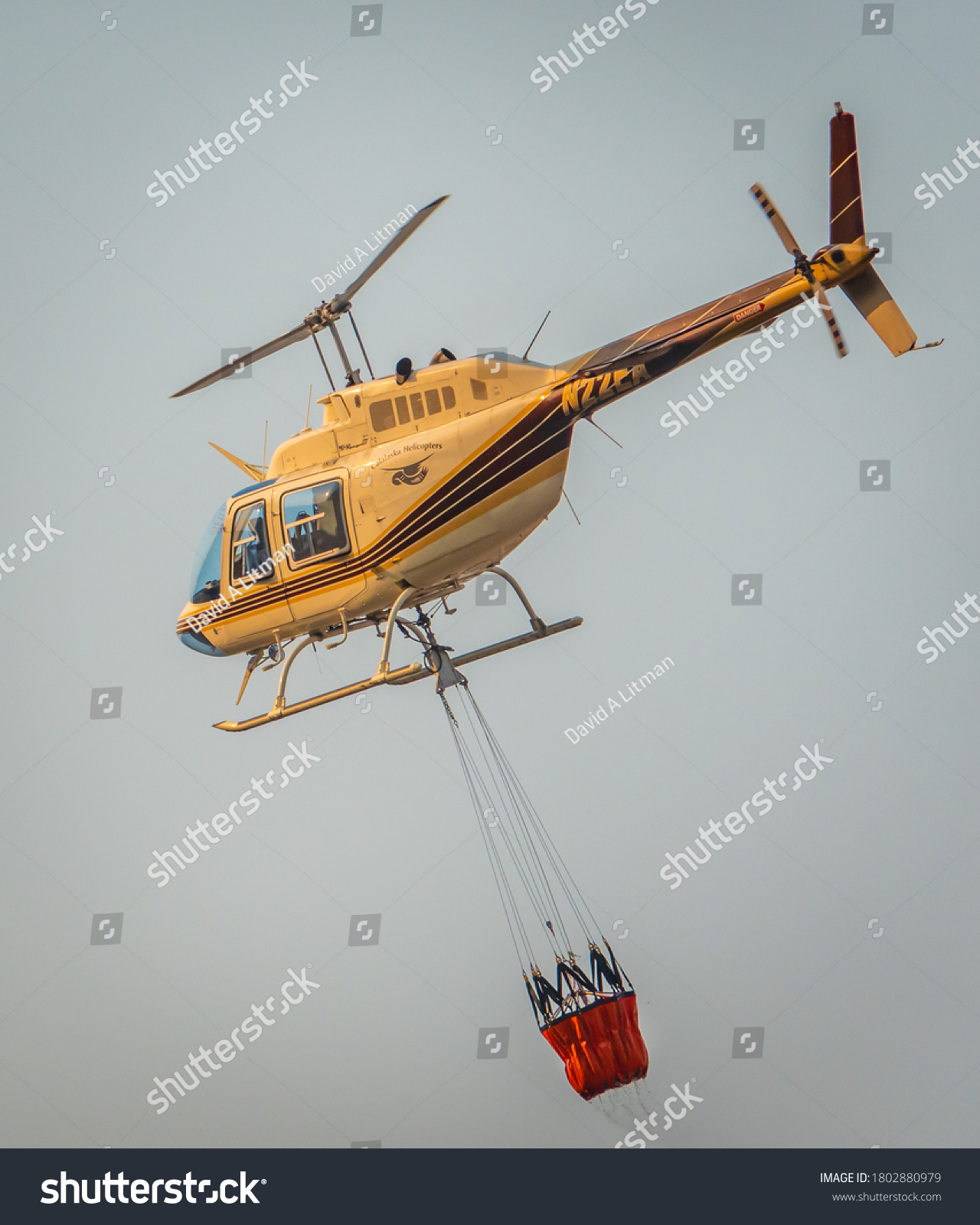 stock-photo-salinas-california-august-a-cal-fire-helicopter-pilot-carries-a-bucket-of-water-to-1802880979.jpg