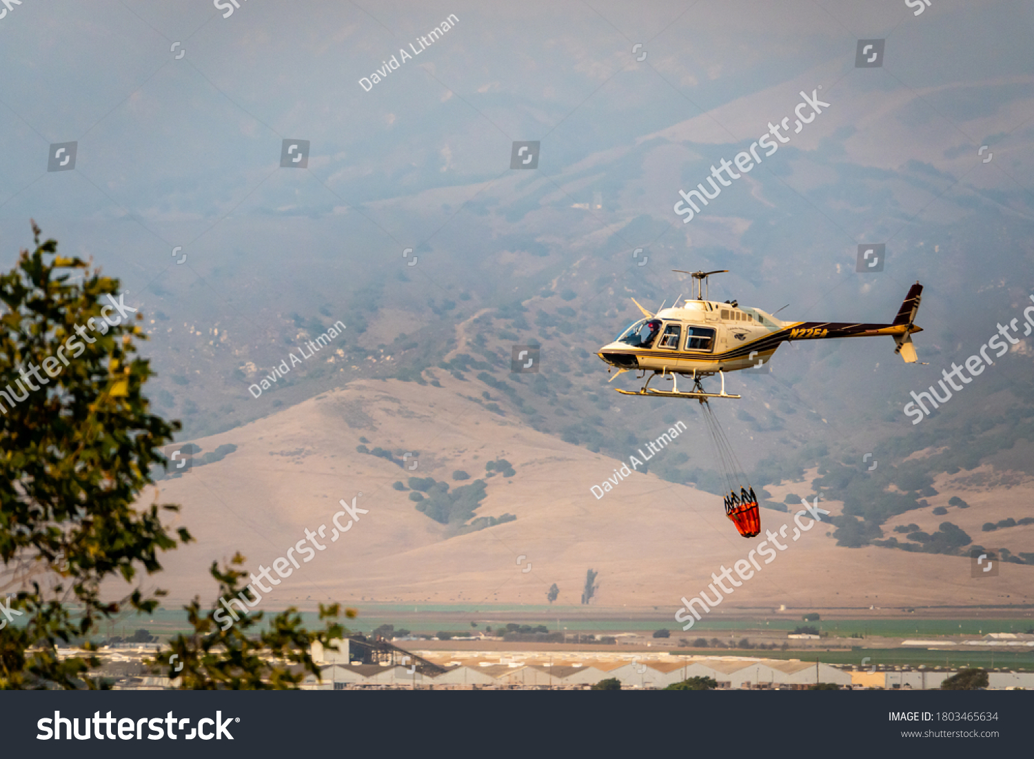 """Salinas, California - August 17, 2020:  A Cal Fire helicopter pilot carries a bucket of water to douse the """"River Fire"""" in the hills of the Salinas Valley of Monterey County of the central coast."""