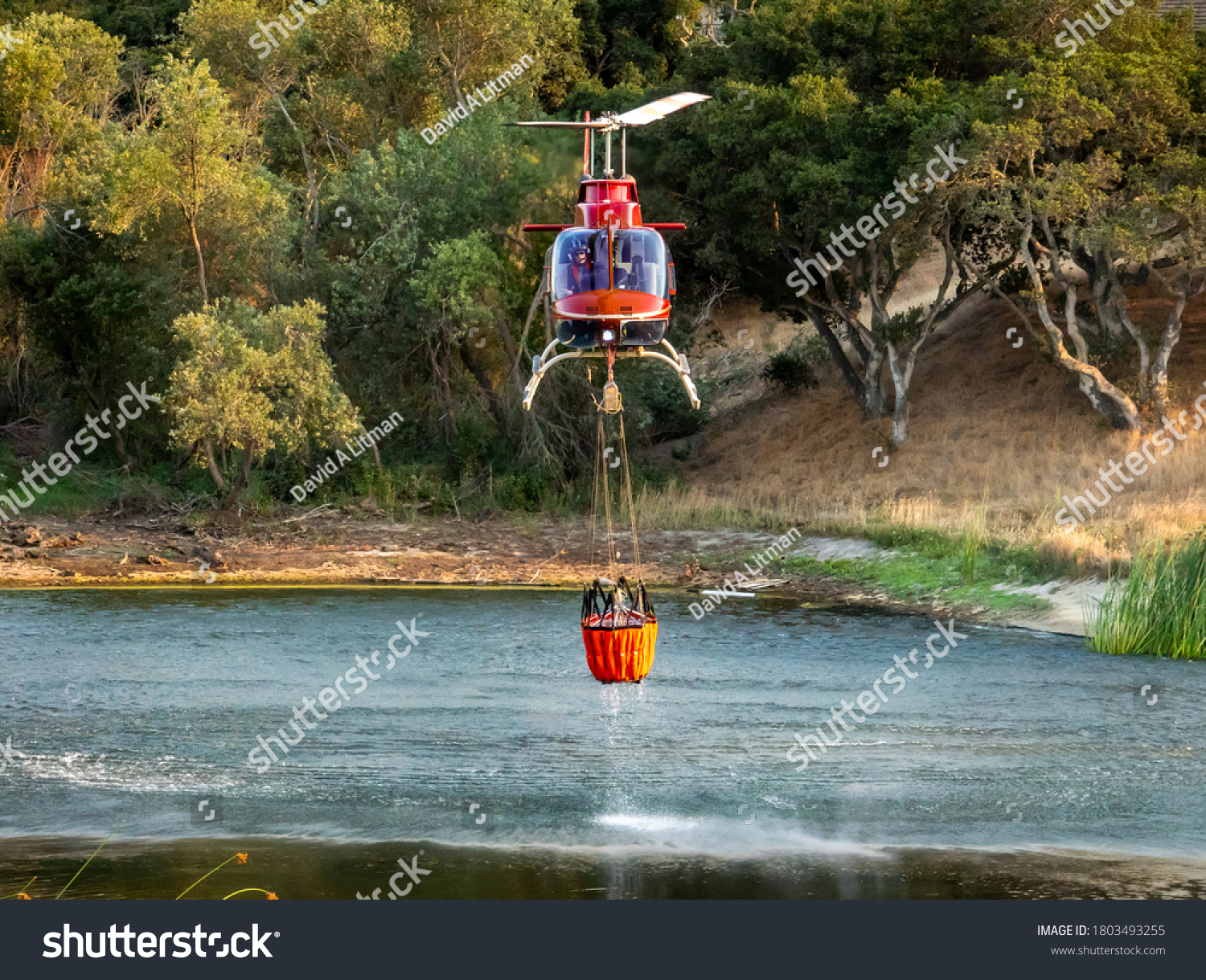 """Salinas, California - August 17, 2020:  A Cal Fire helicopter pilot collects a bucket of water from a pond to douse the """"River Fire"""" in Monterey County of the central coast."""
