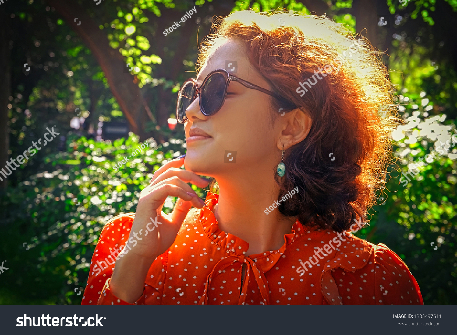 Asian girl in sunglasses looking up closeup of the face. She is posing in rays of bright sun in profile.