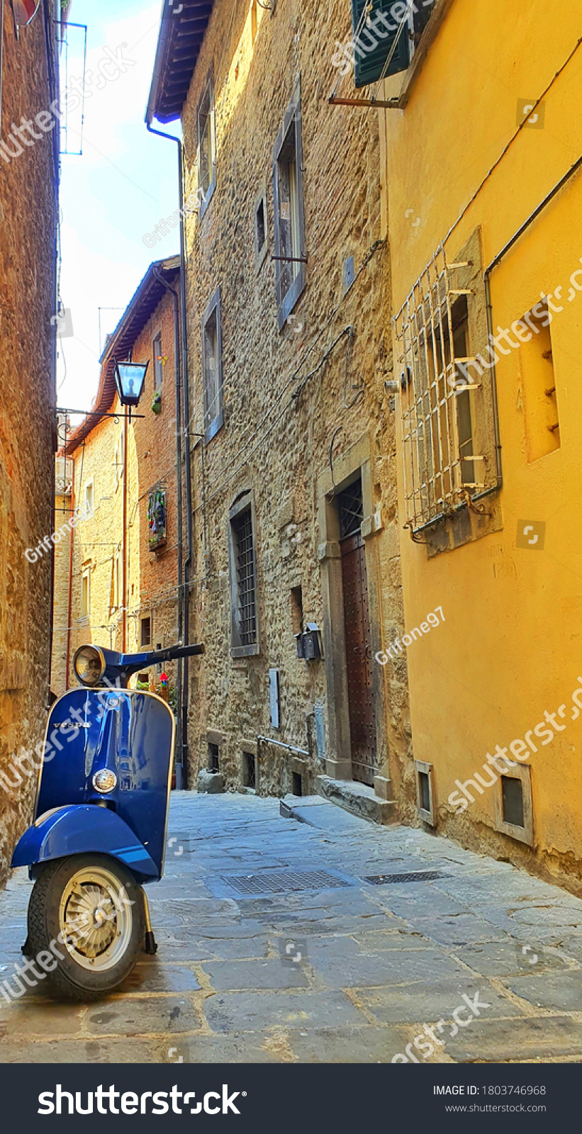 Cortona, Italy - August 18 2020: Vintage scooter Vespa Piaggio parked in a beautiful alley.