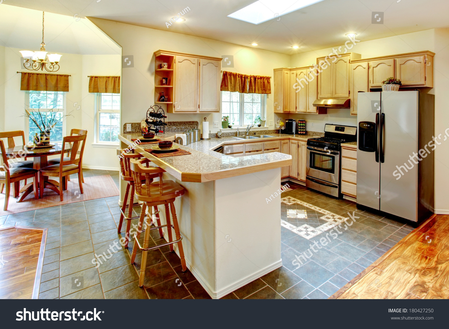 Bright Kitchen Room With Maple Storage Cabinets And Stainless Steel Appliances View Of Dining Area