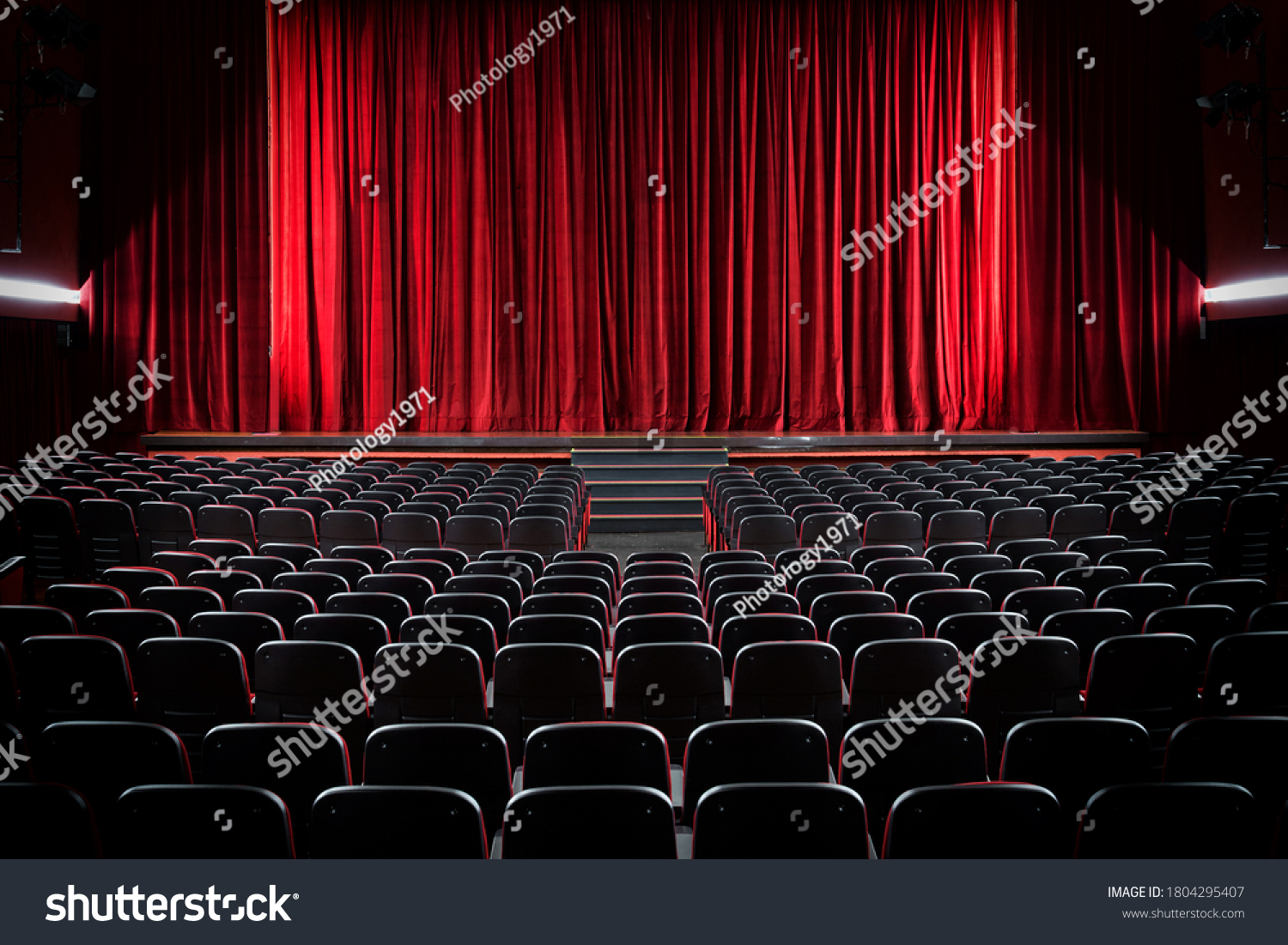 Darkened empty movie theatre and stage with the red curtains drawn viewed over rows of vacant seats from the rear #1804295407