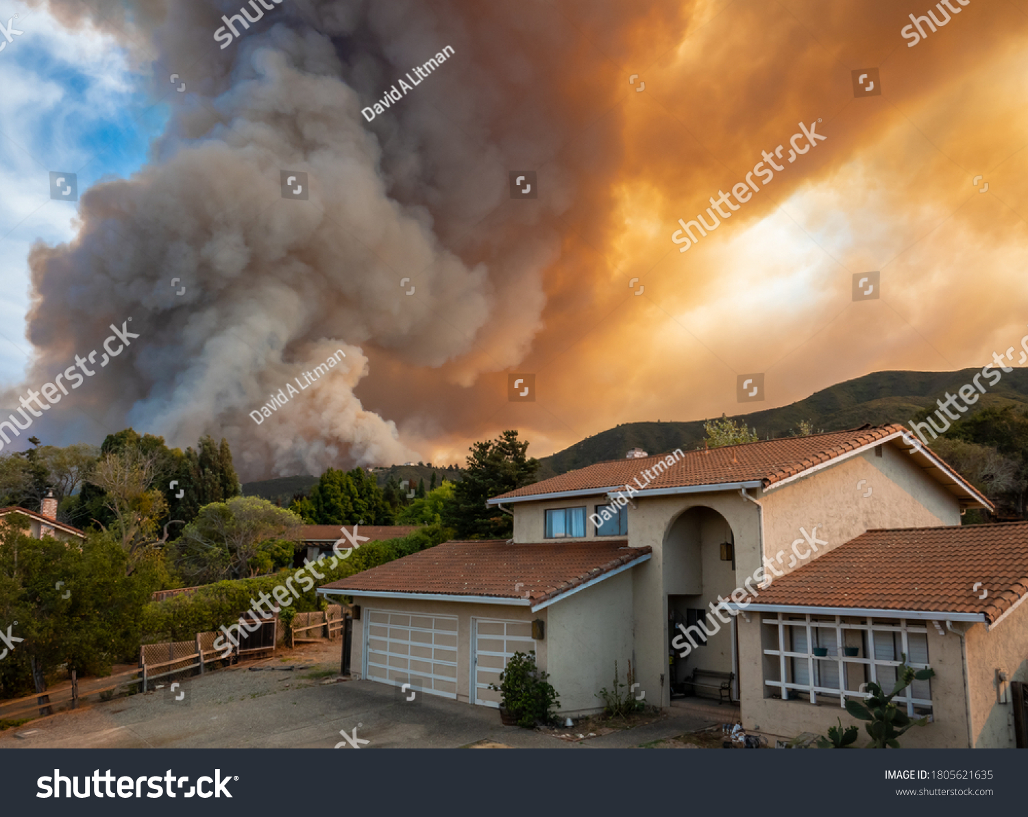 "The California ""River Fire"" of Salinas,  in Monterey County, was ignited by dry lightning on August 16, 2020, fills the sky with dark smoke and flames as it burns close to a houses on its first day."