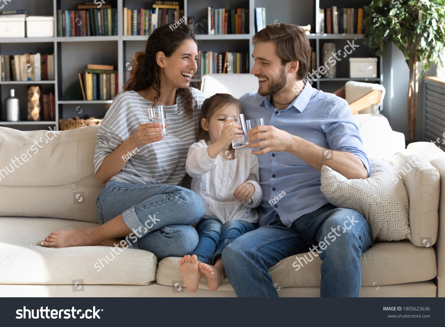 Happy young couple parents teaching little preschool daughter drinking clear water every day. Smiling healthy family holding glasses with pure aqua, enjoying morning daily healthcare habit at home. #1805623636