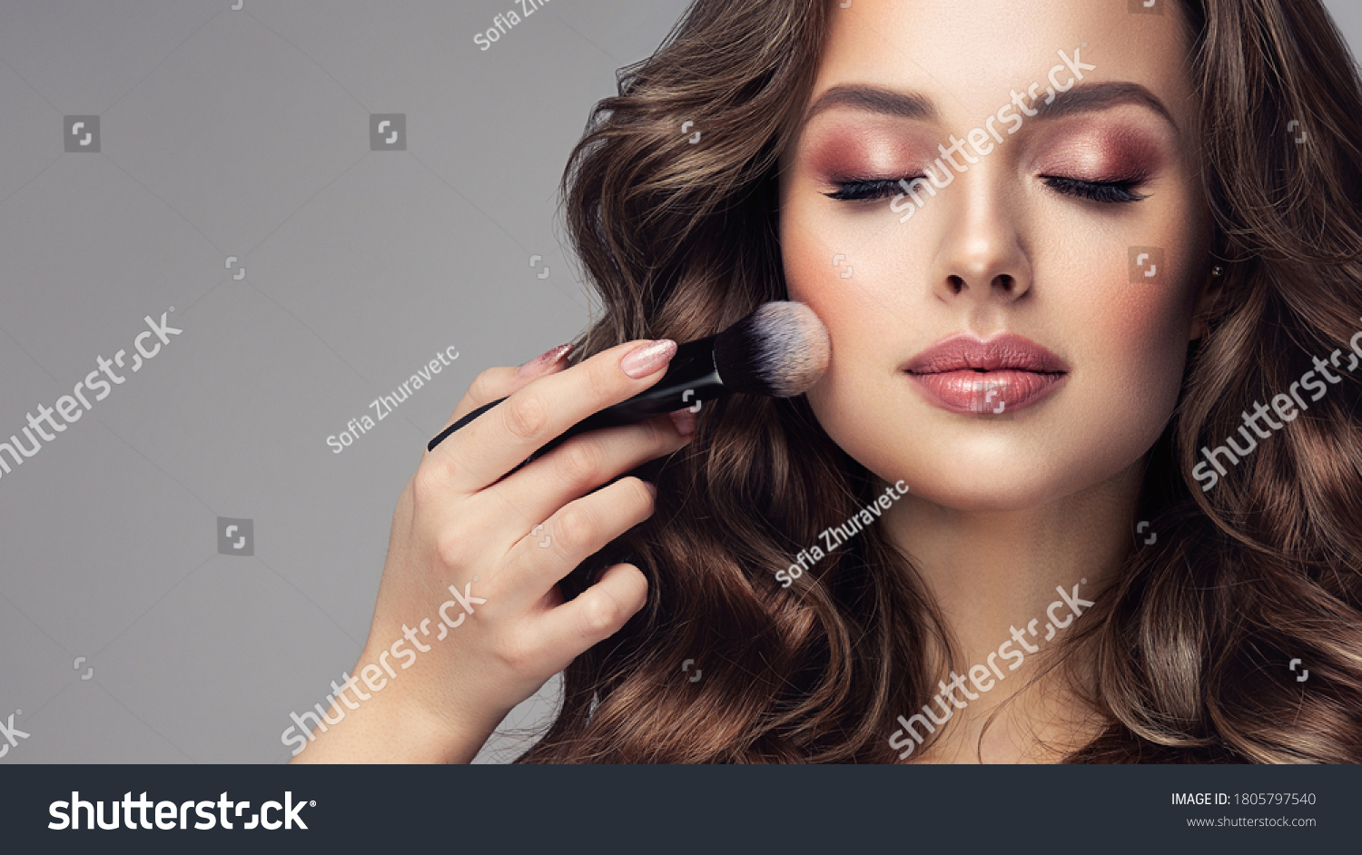 Makeup artist applies   applies powder and blush  . Beautiful woman face. Hand of make-up master puts blush on cheeks  beauty  model girl . Make up in process #1805797540