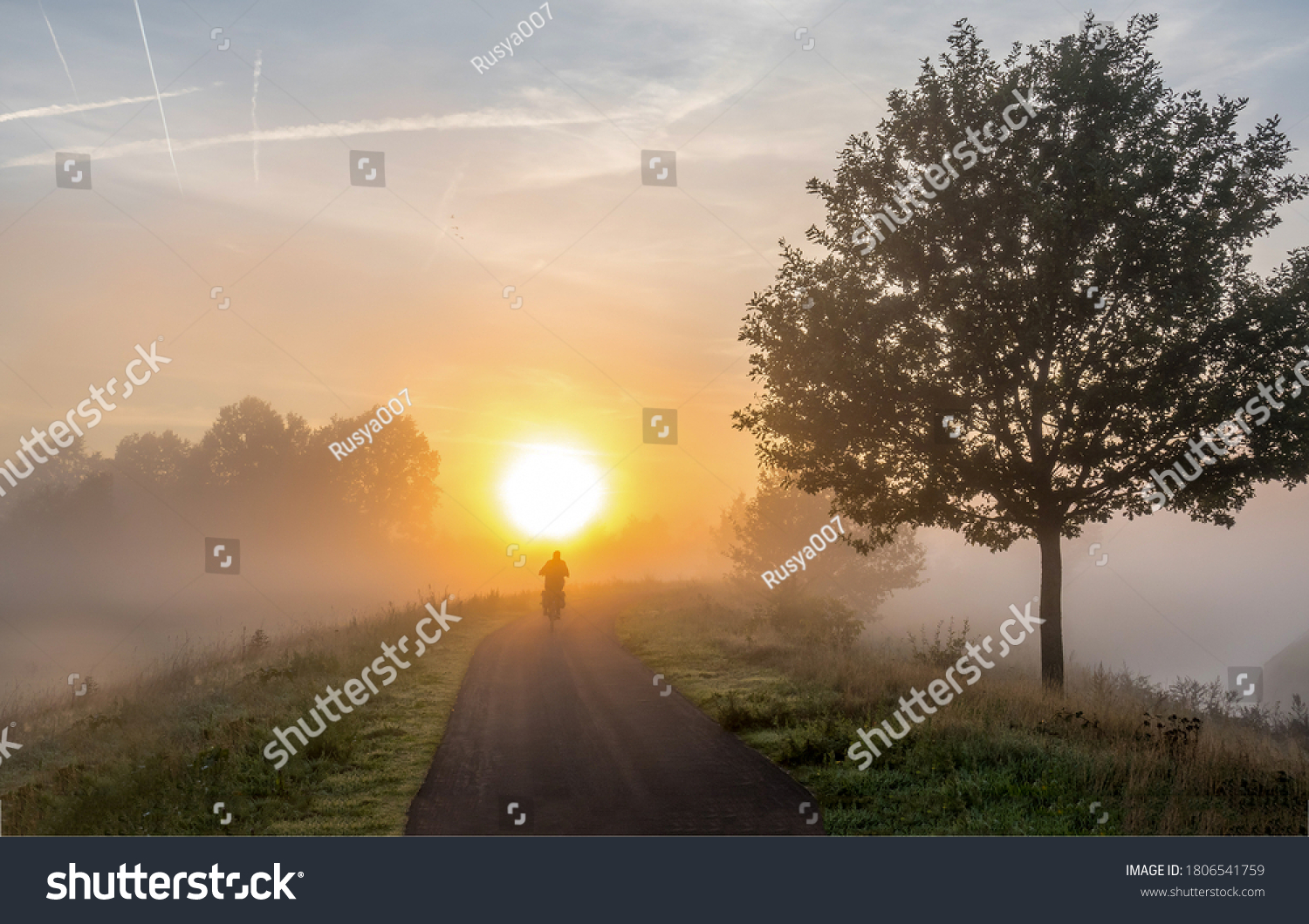 Sunrise fog silhouette of a cyclist. Ealy morning mist trip. Early morning sunrise travel. Sunrise in early morning #1806541759