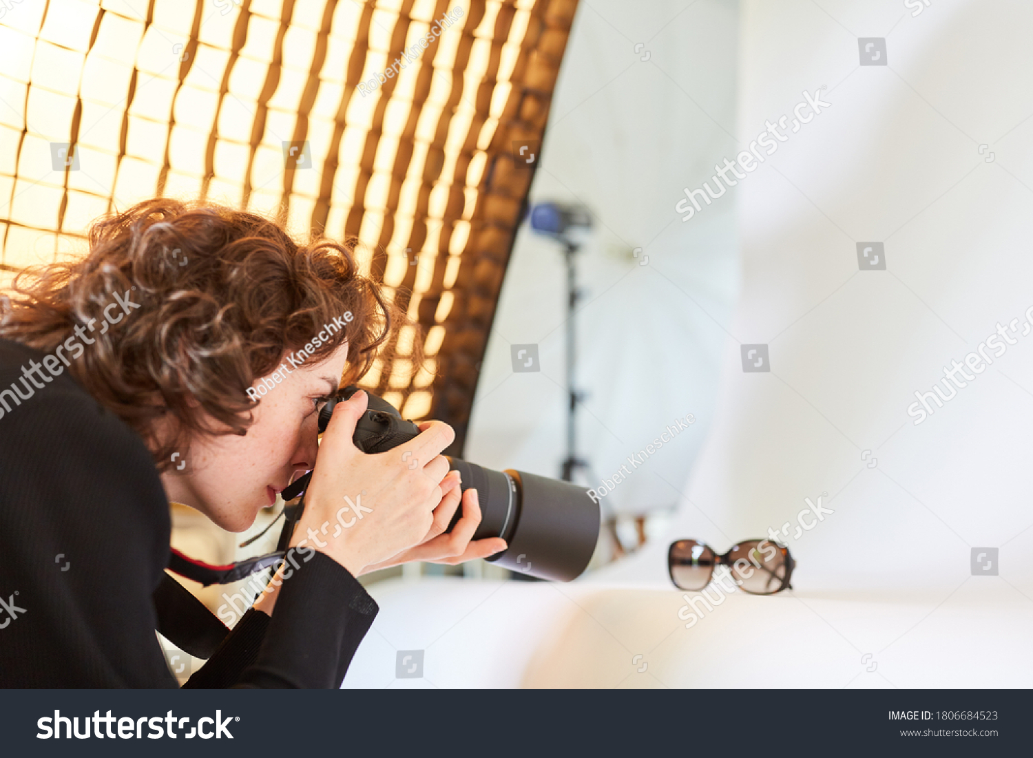 Photographer with camera photographs a pair of glasses for product photography #1806684523