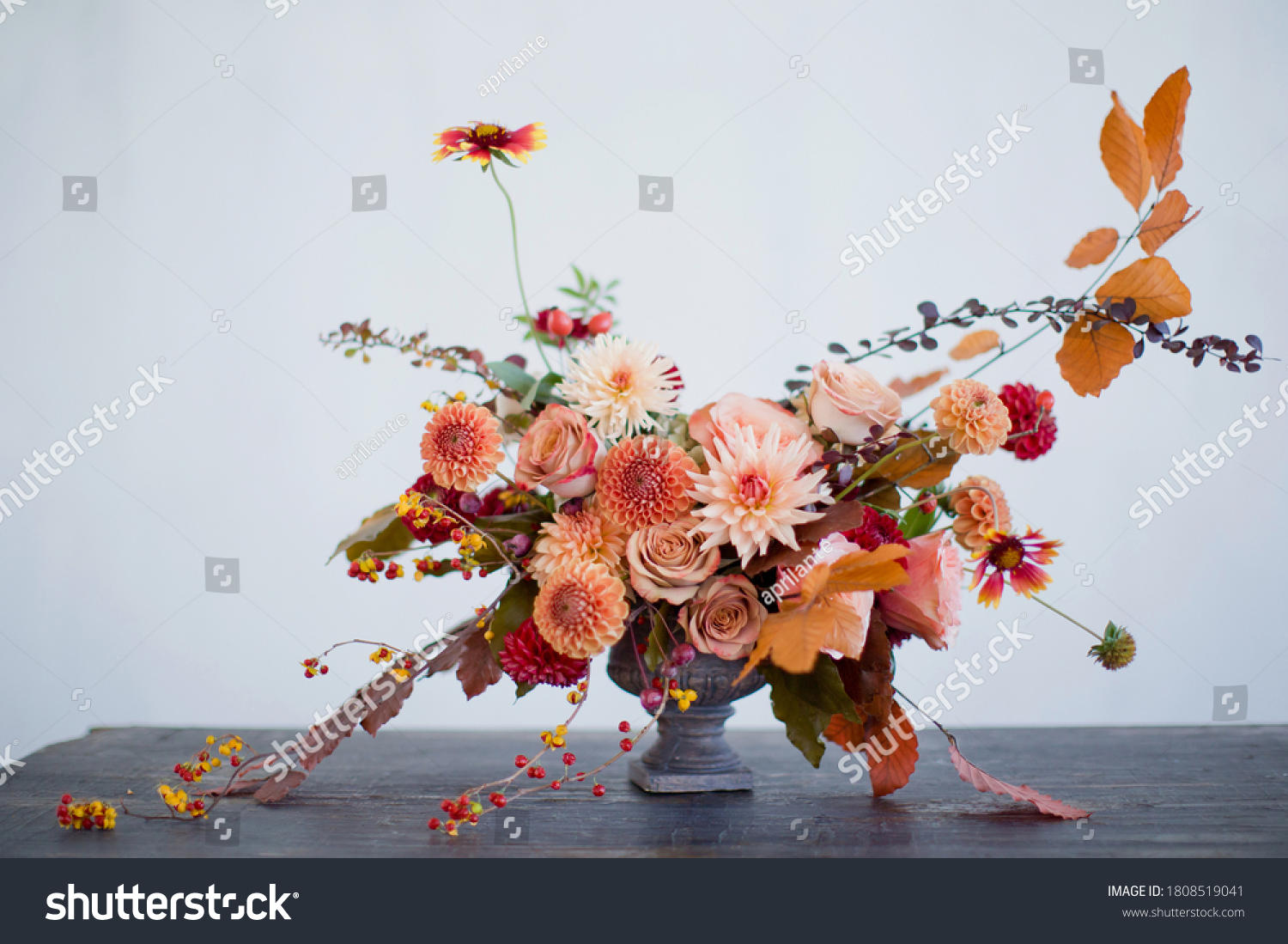 Beautiful flower composition with autumn orange and red flowers and berries. Autumn bouquet in vintage vase on a white wall background #1808519041