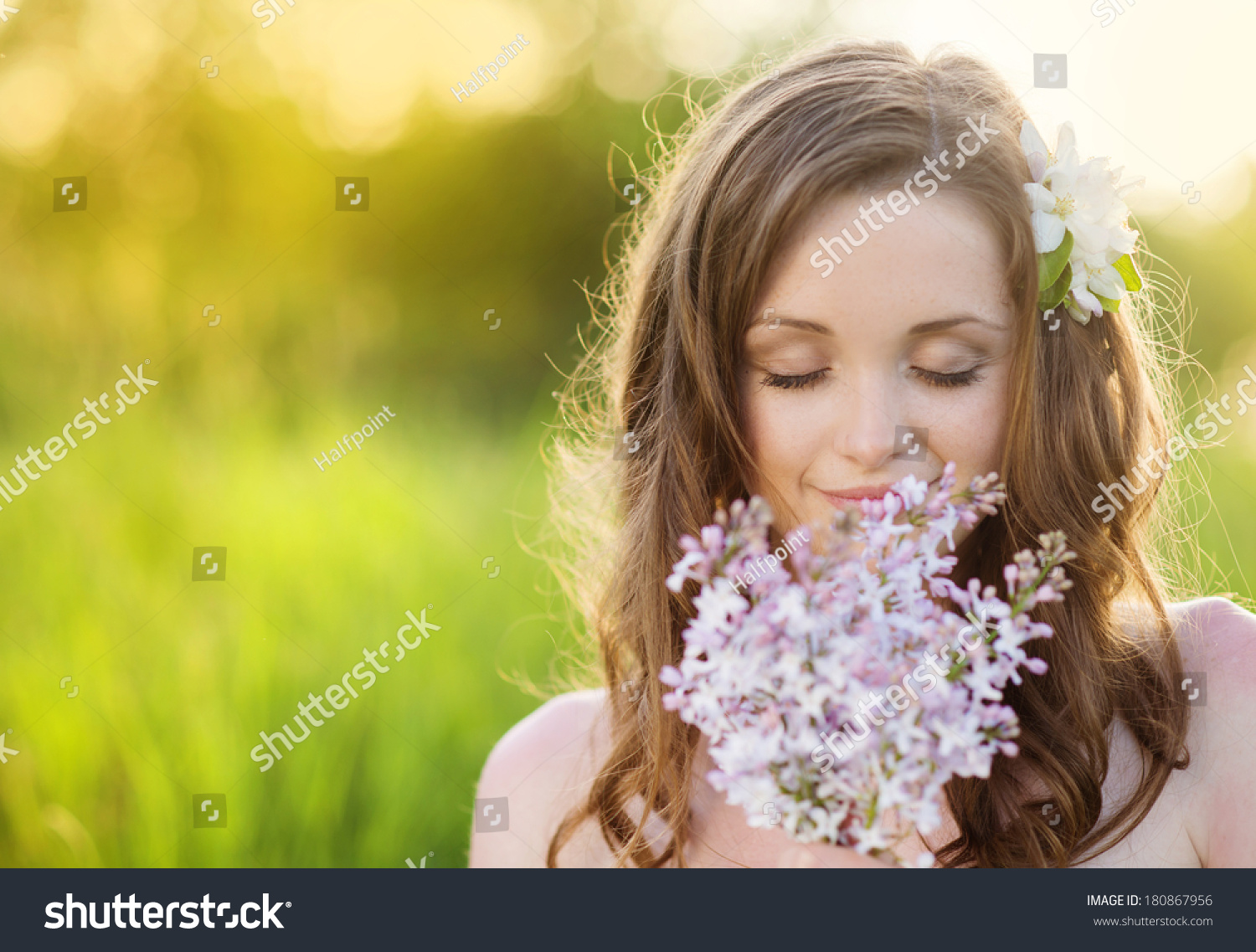 Royalty free beautiful woman with flowers in spring 180867956 beautiful woman with flowers in spring sunshine girl is holding a lillac on the green izmirmasajfo