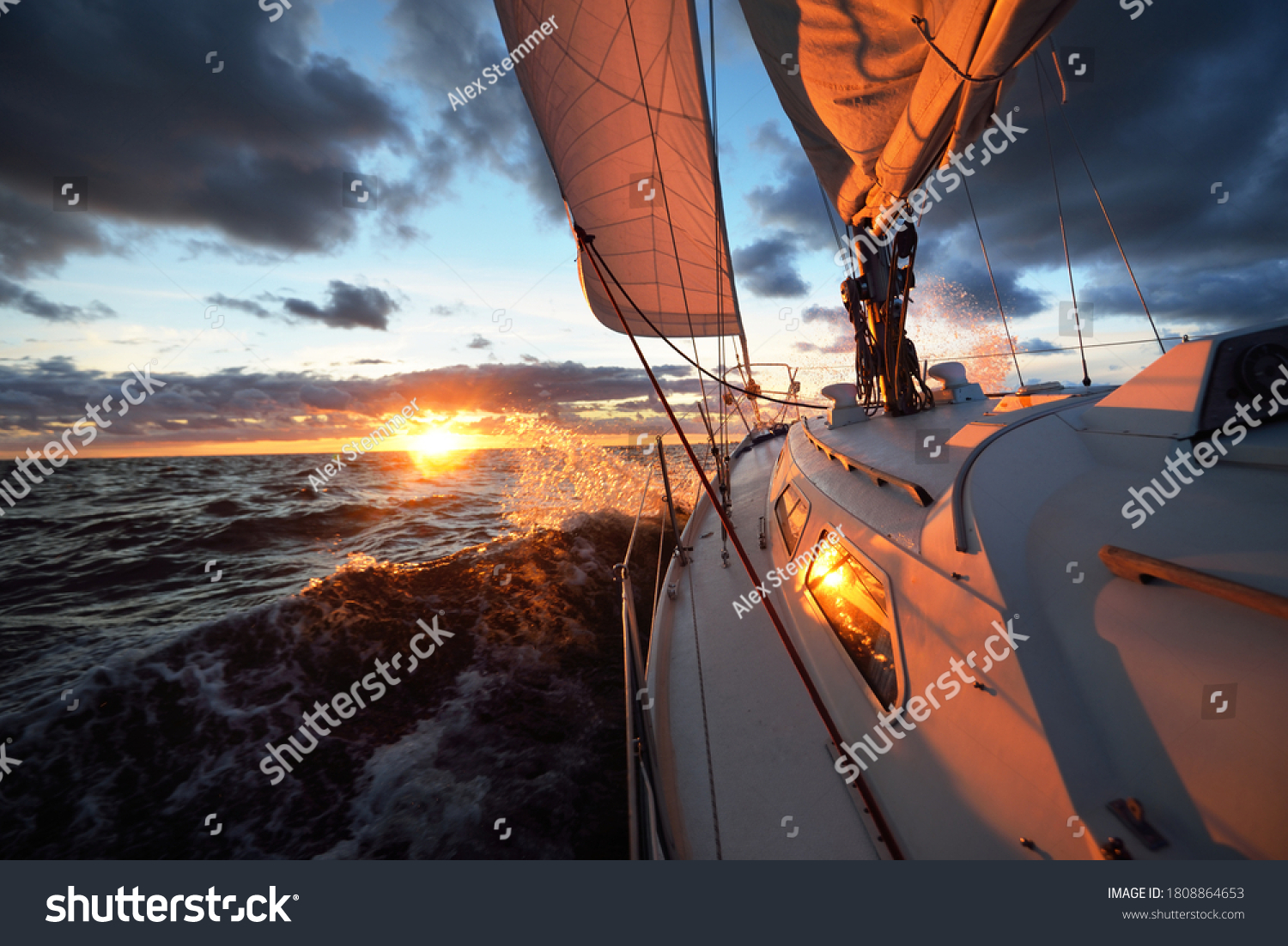 Yacht sailing in an open sea at sunset. Close-up view of the deck, mast and sails. Clear sky after the rain, dramatic glowing clouds, golden sunlight, waves and water splashes, cyclone. Epic seascape #1808864653