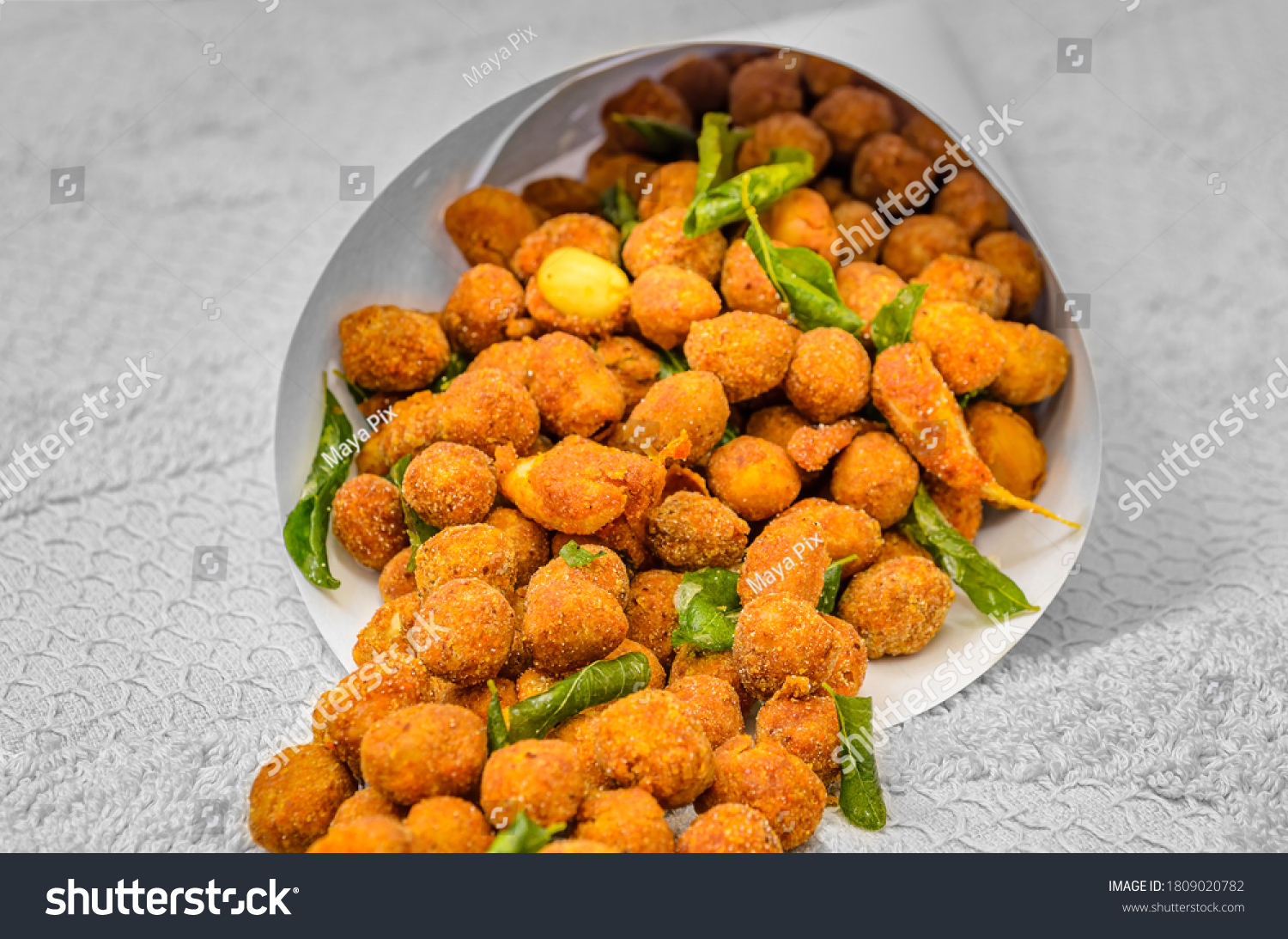 Traditional Indian snack - Masala Peanuts  with Fried Curry Leaves in a Paper Cone
