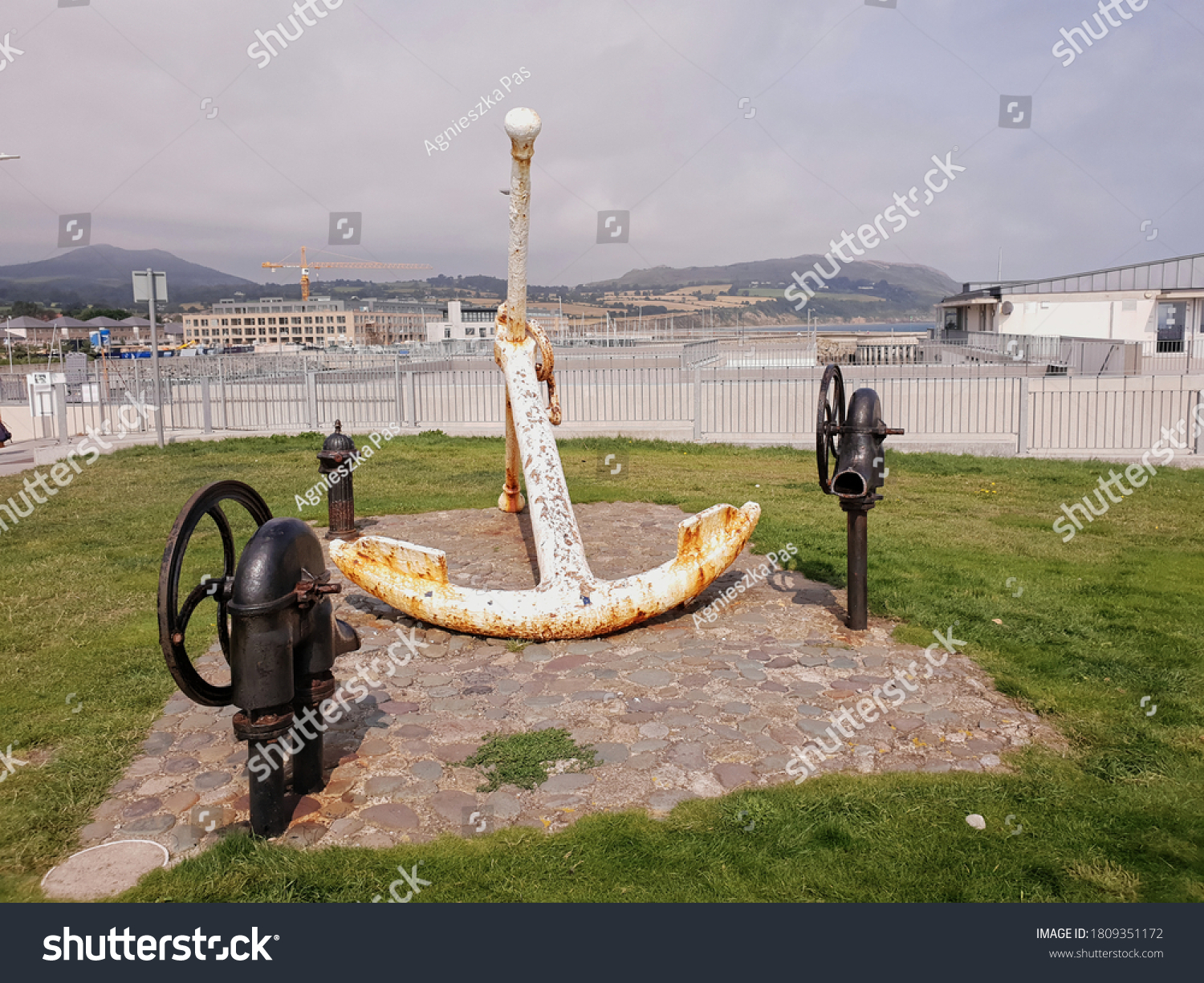 GREYSTONES, CO. WICKLOW, IRELAND - AUGUST 09, 2020: Anchor monument in the port in Greystones town. Wicklow mountains in the background. Cloudy summer day.