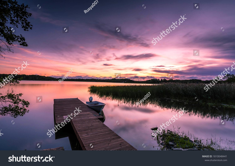 Sunset lake pier landscape. Lake pier at sunset. Sunset lake pier boat. Boat at sunset lake pier #1810048441