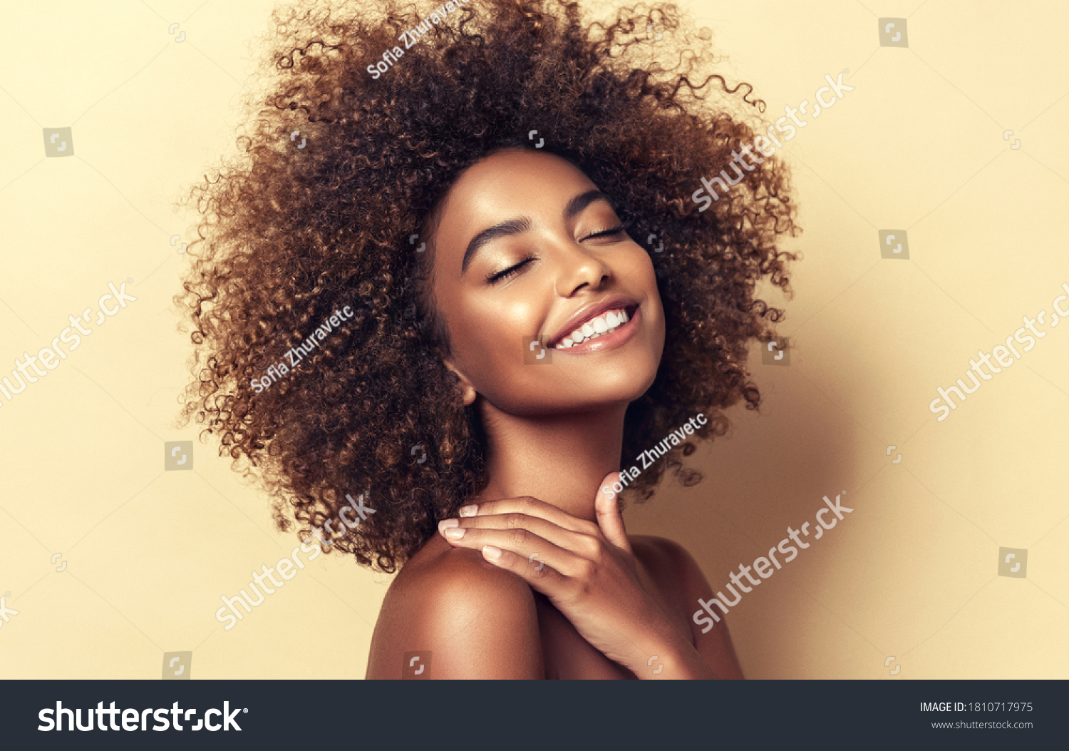Beauty portrait of african american woman with clean healthy skin on beige background. Smiling dreamy beautiful afro girl.Curly black hair #1810717975