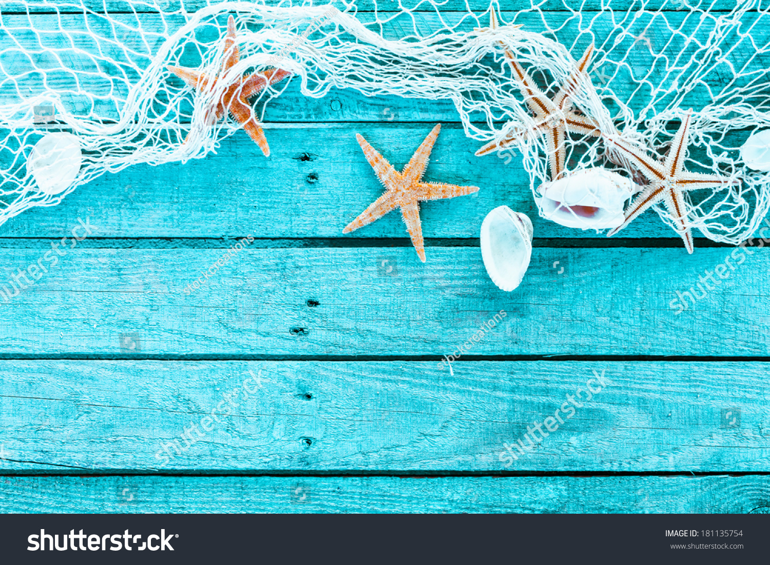 Delicate nautical border with fishing net, sea shells and starfish on a background of colourful turquoise blue painted wooden boards with copyspace for your text #181135754
