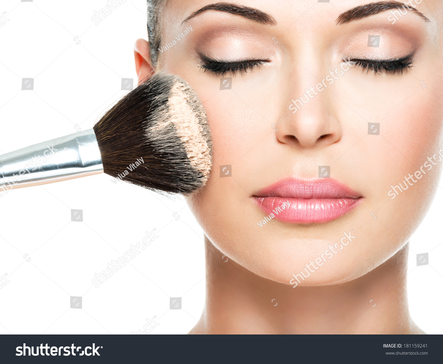 Closeup portrait of a woman  applying dry cosmetic tonal foundation  on the face using makeup brush.  #181159241