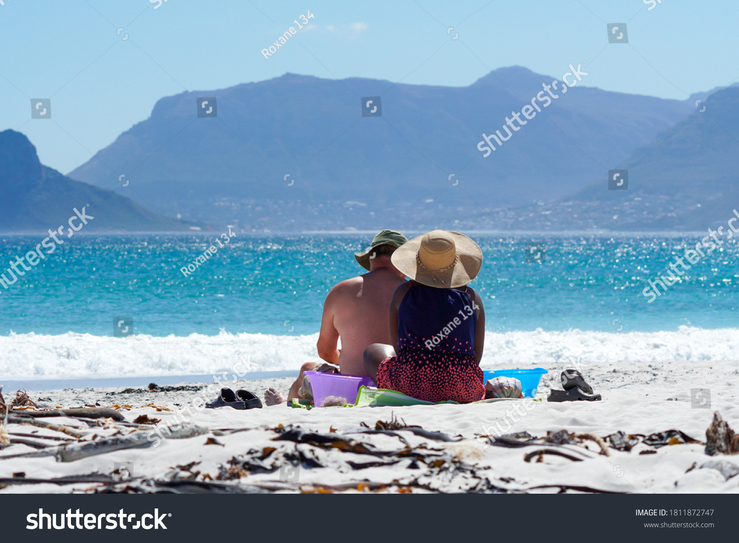 a couple, man and woman, sitting on a beach, with the view of mountains and blue ocean in front of them