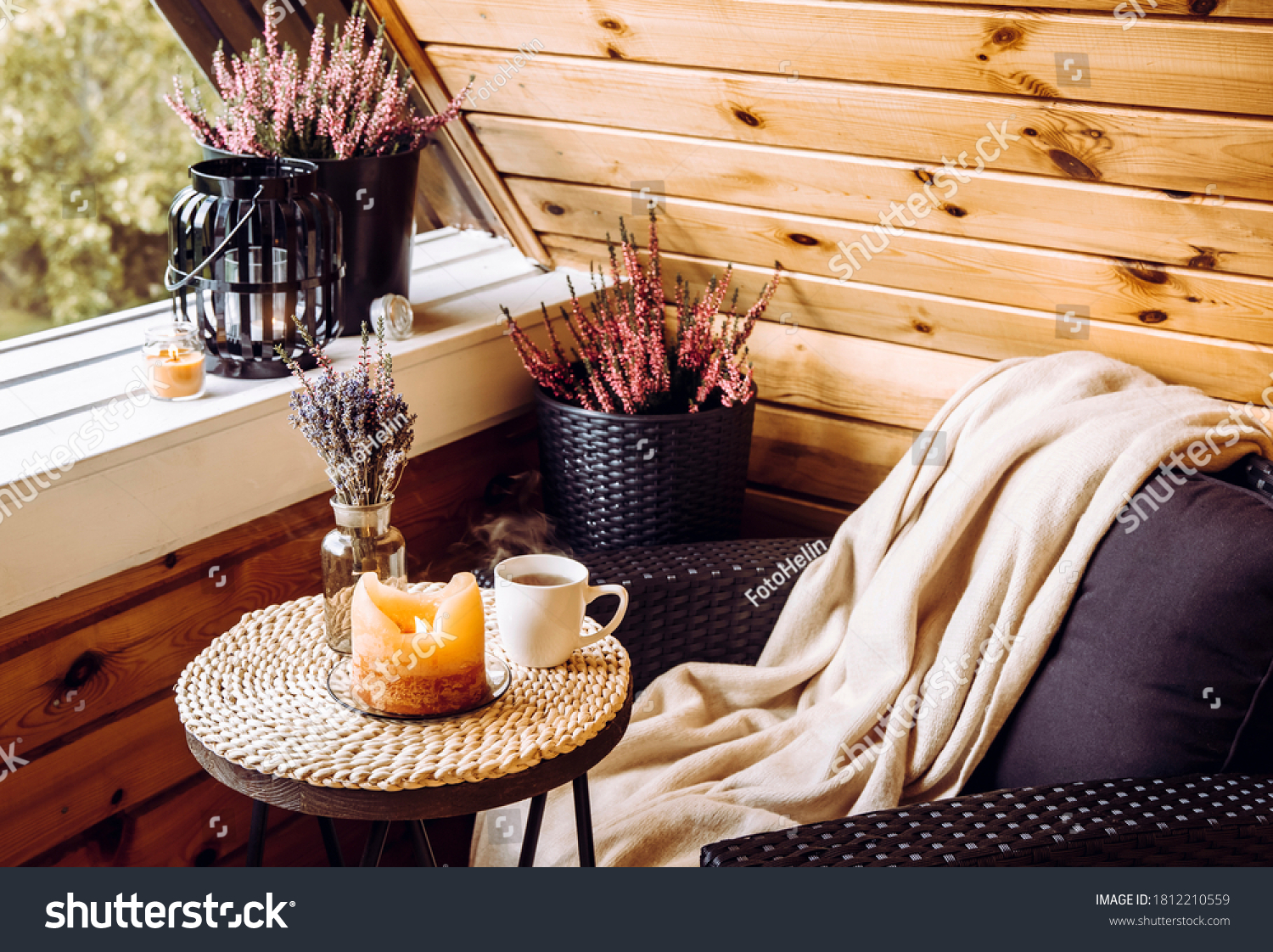 Cute autumn hygge home decor arrangement. Tiny wooden cabin balcony with heather flowers, lavender in bottle vase, candlelight flame, soft beige plaid waiting on comfortable garden furniture chair. #1812210559