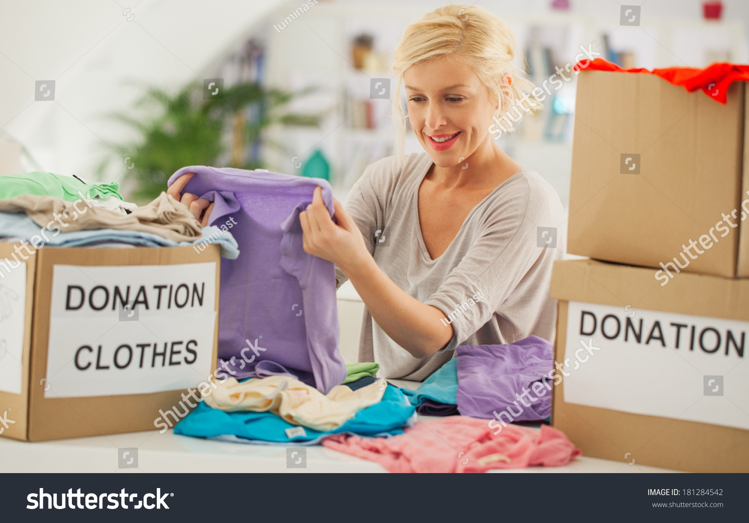 Woman preparing old clothes she wants stock photo for Shirts that donate to charity