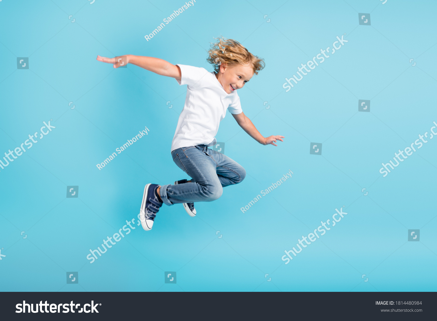 Profile photo of young boy jump fly movement hands wear white shirt jeans sneakers isolated blue color background #1814480984