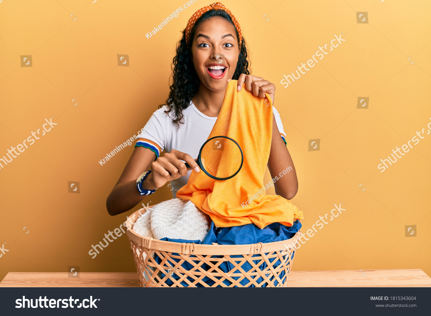 Young african american girl holding magnifying glass looking for stain at clothes celebrating crazy and amazed for success with open eyes screaming excited.  #1815343604