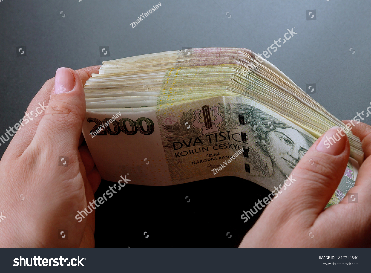 Bundle of Czech money in the hands of a woman. Banknotes of 2000. Czech crowns. #1817212640