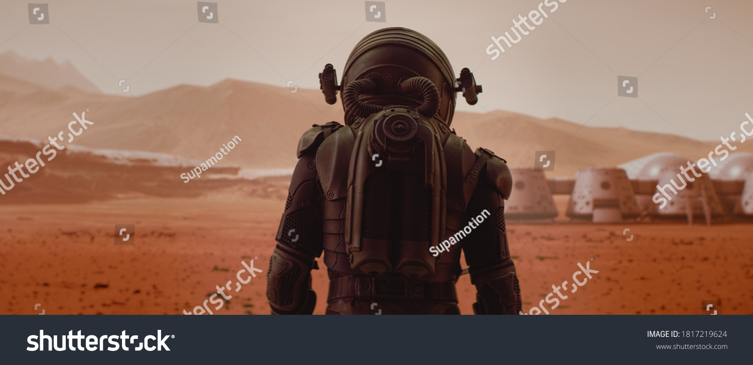 Back view of astronaut wearing space suit walking on a surface of a red planet. Martian base and rover in the background. Mars colonization concept #1817219624