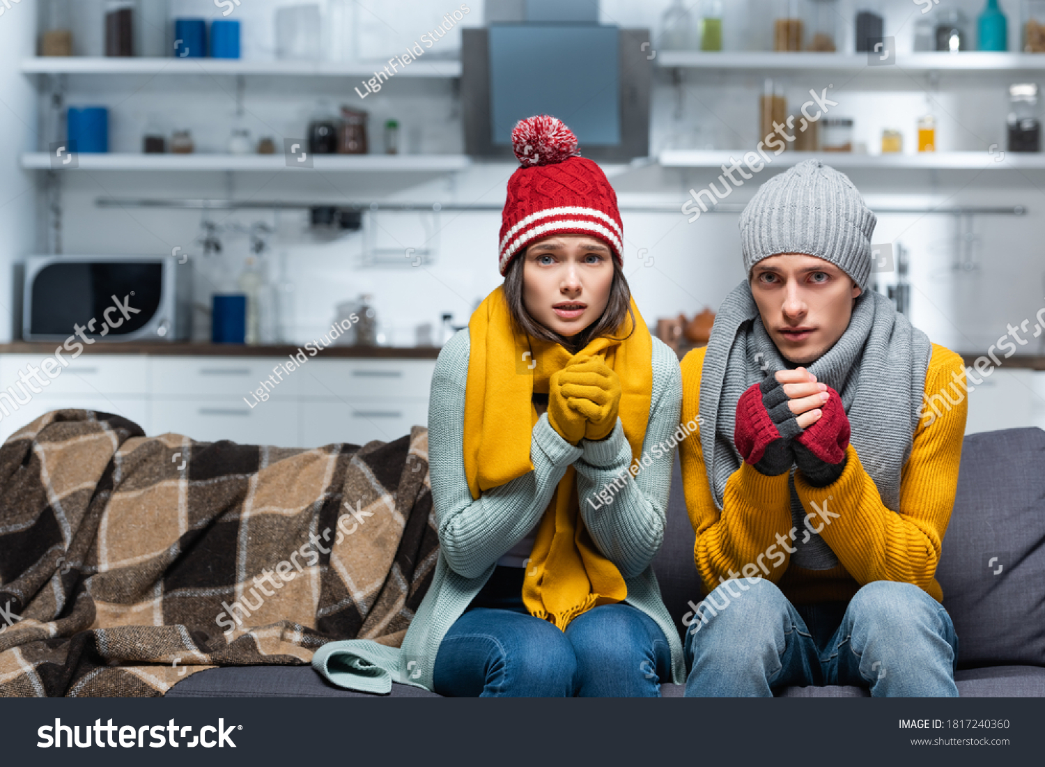 freezing couple in warm hats and gloves looking at camera while sitting on sofa in cold kitchen #1817240360