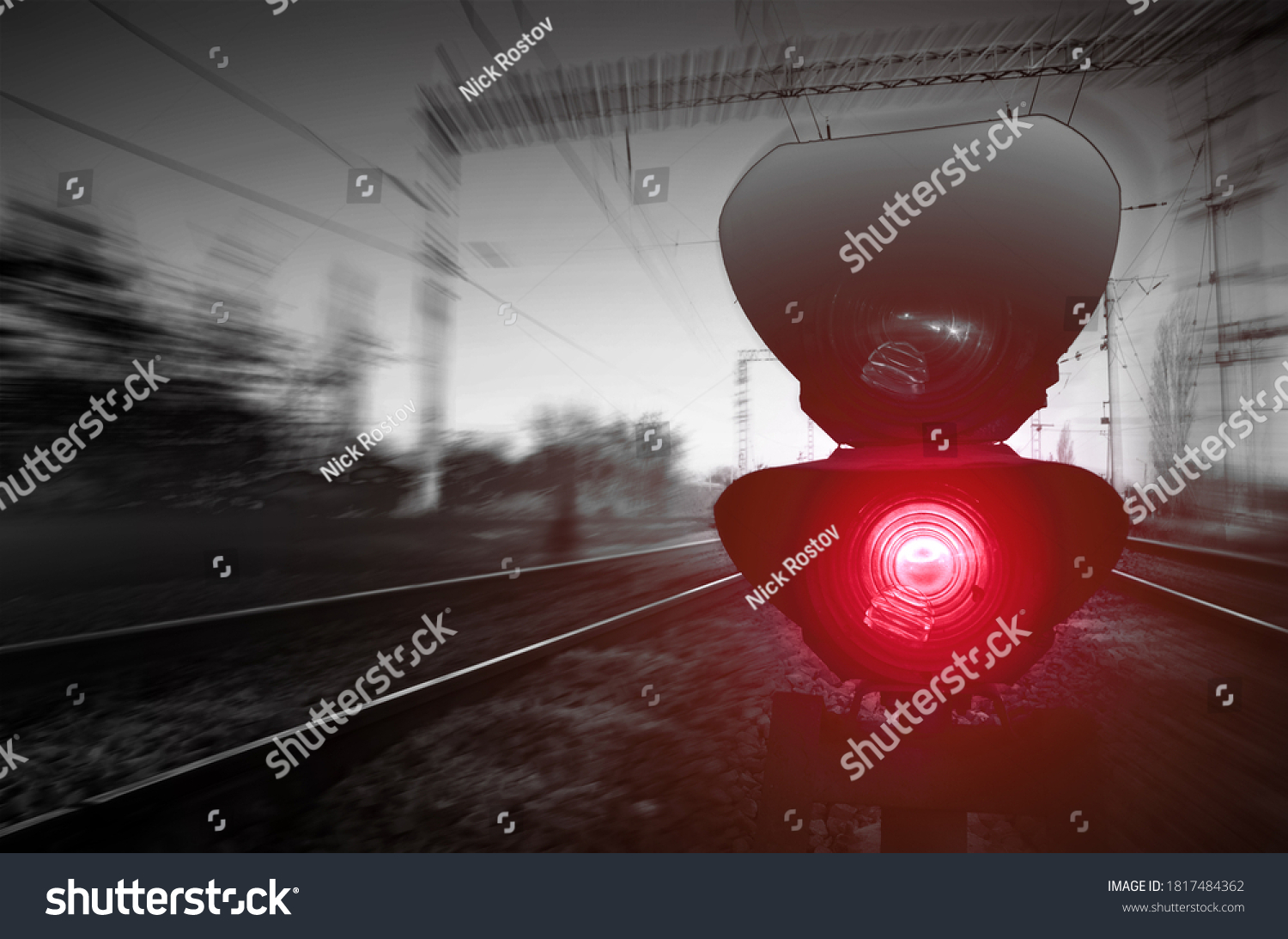 Railroad crossing and red light traffic light. Motion blurred background.