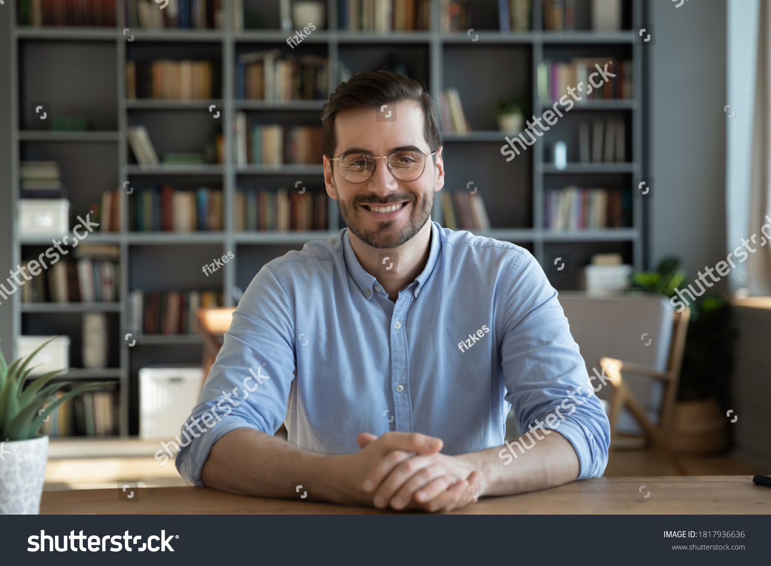 Headshot portrait of smiling 30s Caucasian millennial man in glasses sit at desk at home talk speak on video call or webcam virtual conference. Picture of happy young male in spectacles pose at table. #1817936636